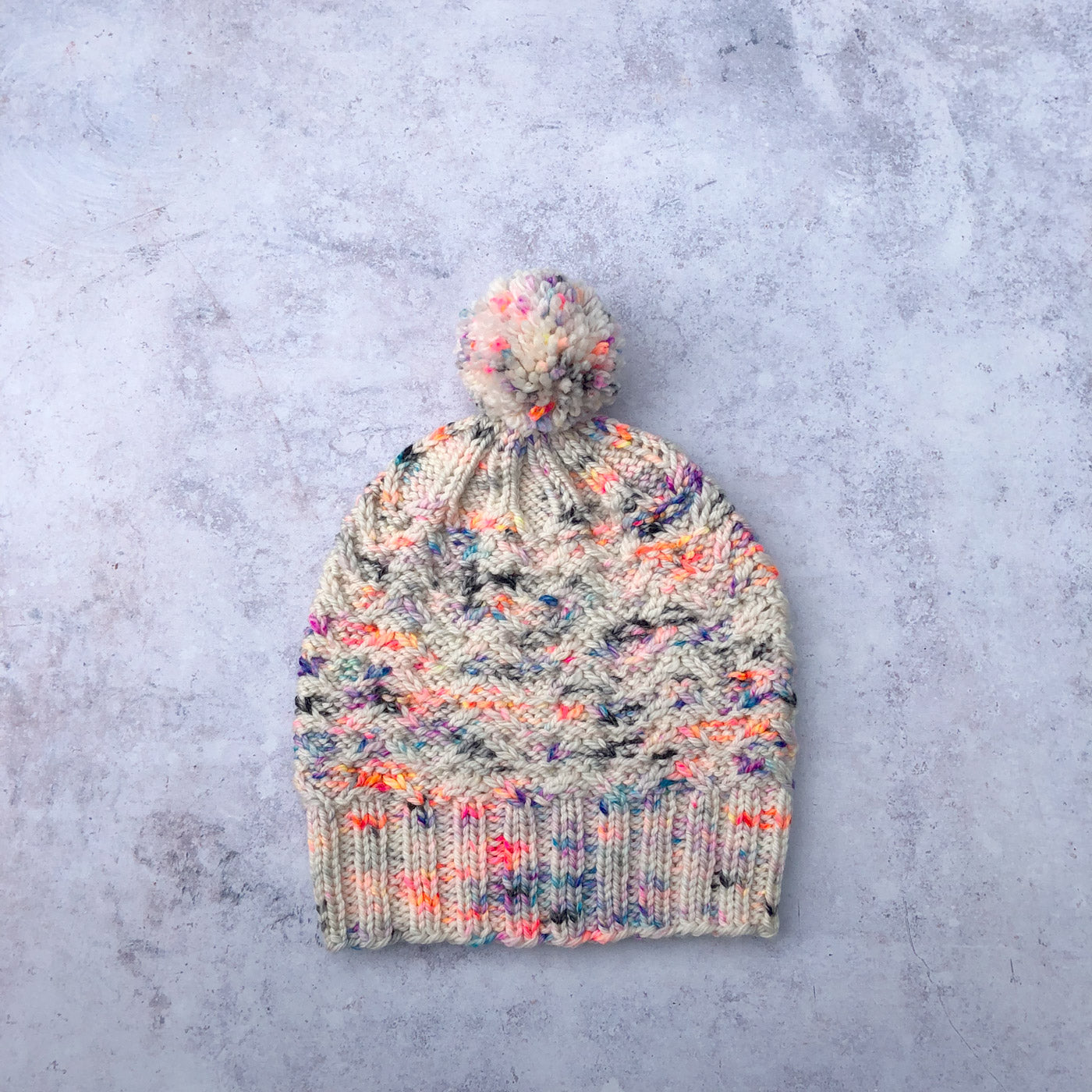 Handknit hat laying flat, it has textured stitches in white yarn speckled with coral, purple and blue. There is a pom-pom on top made from the same yarn.