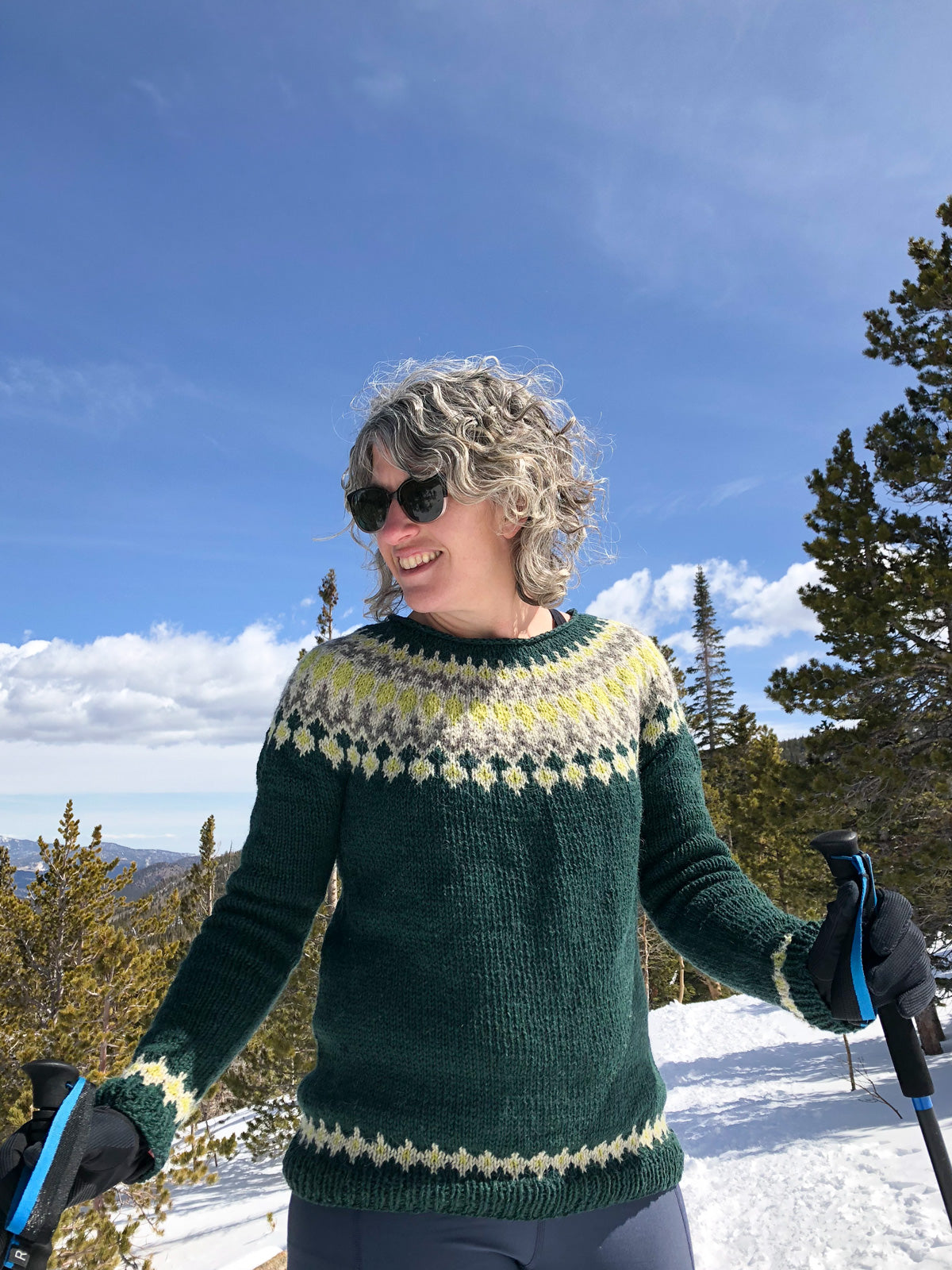 Close up of Jaime holding her hiking poles in her Navia Treysta sweater