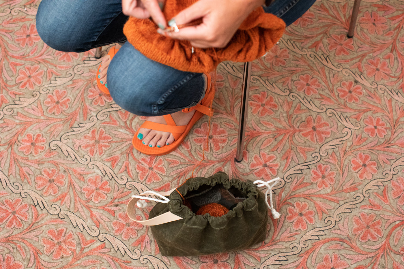 This is an image of a person's hands knitting with a work bag on the floor on top of an orange and tan rug