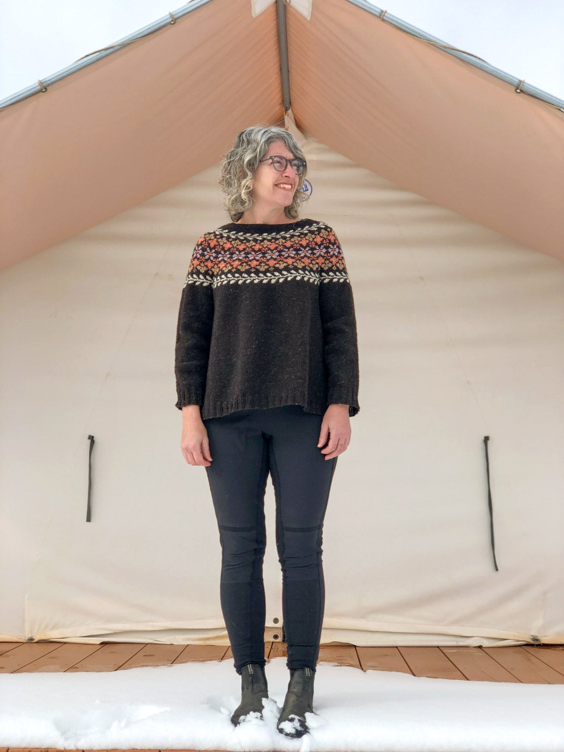 Jaime standing in front of a cream canvas tent in her freshly finished Birkin Sweater