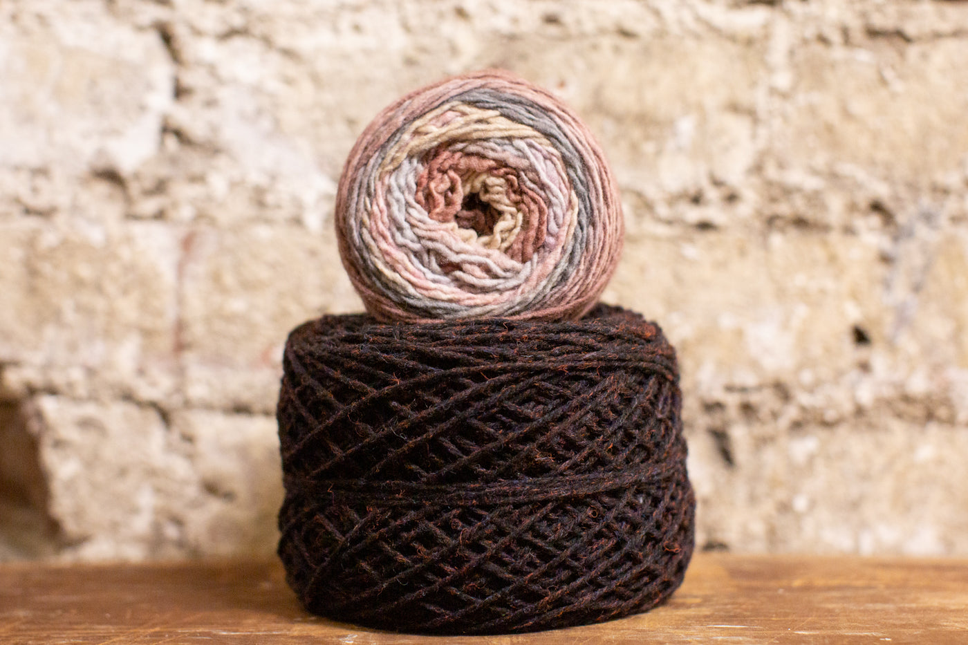 Yarn against sitting on a wooden surface against a whitewashed brick wall.  The yarn is Cottongrass in the beautiful black heather in the color Cinder with Freia flux yarn in an ombre effect in Purpleheart, sitting on top sideways to see the ombre colors.