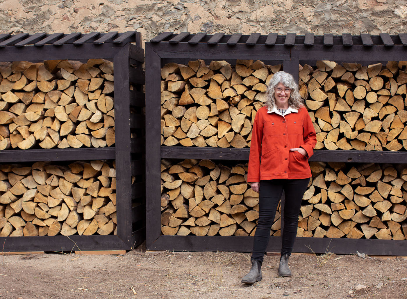 Jaime stands in front of a neatly stacked wall of firewood, wearing her Thayer Jacket in fire-orange twill, black skinny jeans and boots. That is a lot of firewood behind her!