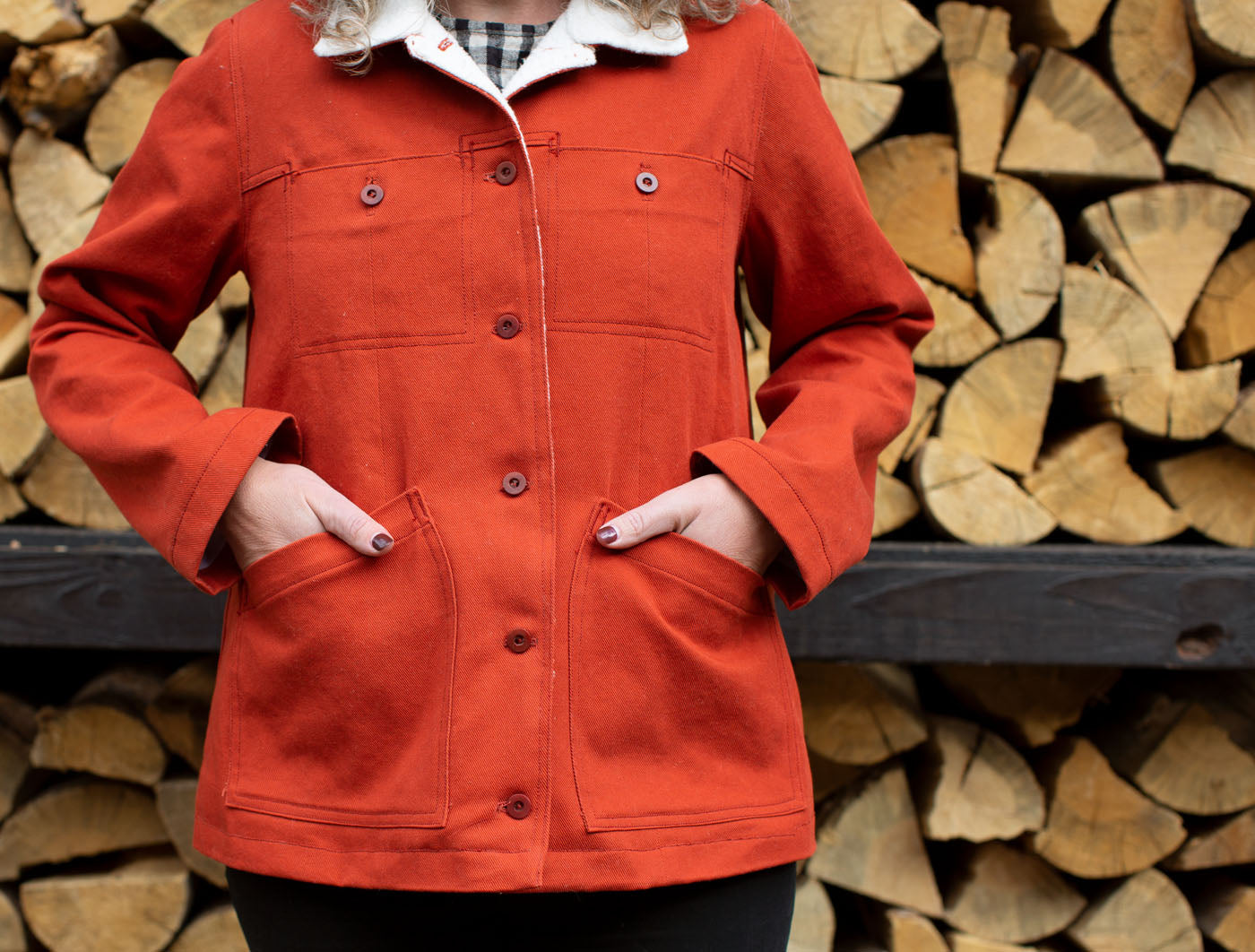 Close up photo of the torso of someone wearing a fiery orange jacket with a white fleece-lined collar. Their hands are in the pockets and they stand in front of a neatly stacked wall of firewood.