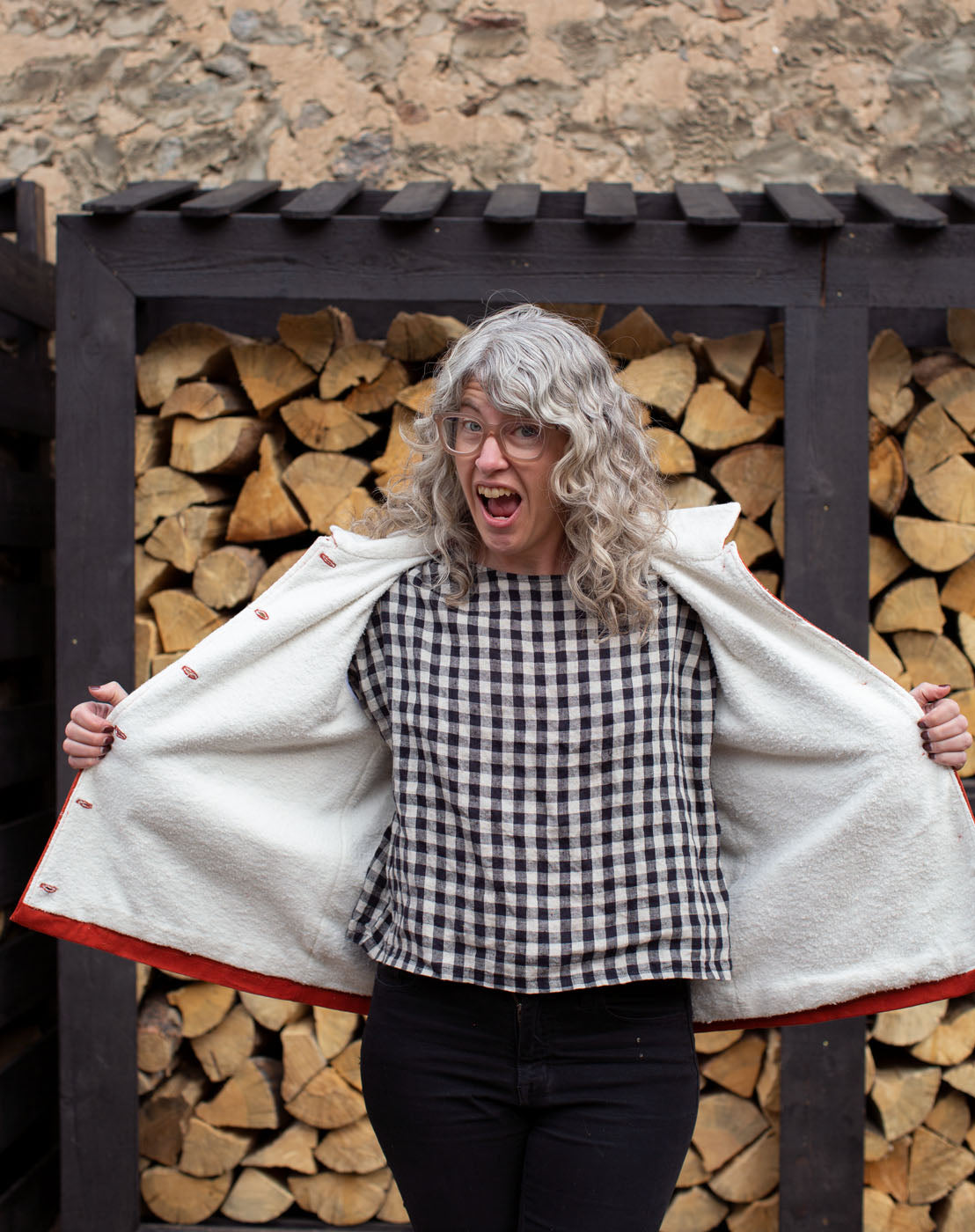 Jaime stands in front of a neatly stacked wall of firewood, holding her Thayer Jacket open to show off the inside. The jacket is lined with hemp/cotton sherpa.