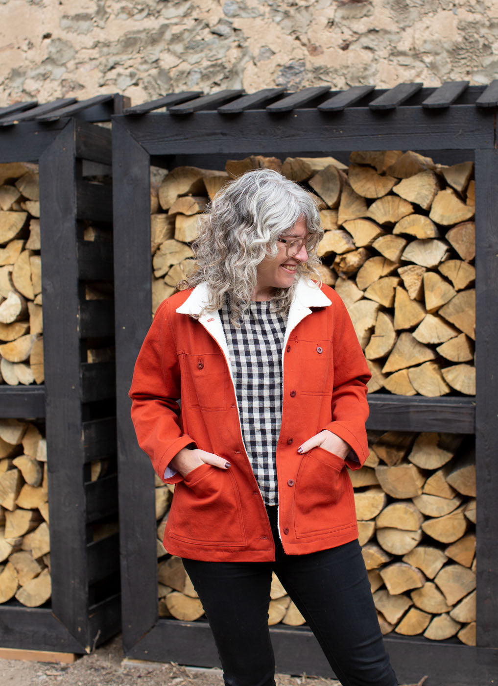 Jaime stands in front of a neatly stacked wall of firewood, wearing her Thayer Jacket in fire-orange twill unbuttoned. The jacket is lined with hemp/cotton sherpa.