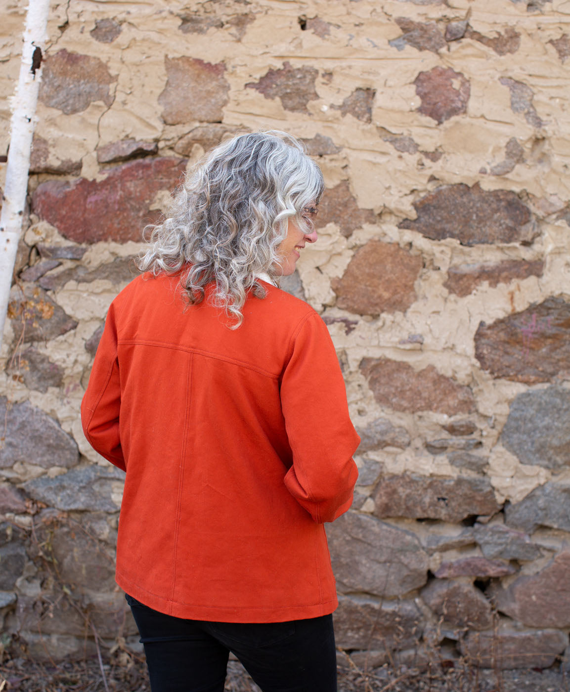 Jaime is standing with her back facing, showing neat seams across and down the back of the jacket. She stands in front of an old stone wall.