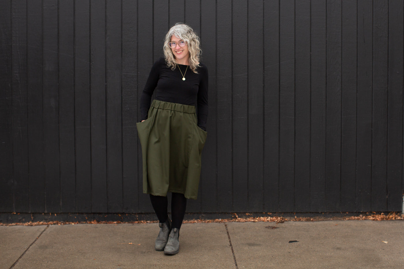 Jaime standing against a black wall looking at the camera smiling.  Jaime is wearing a black long sleeve shirt, olive green skirt, black leggings and black shoes.