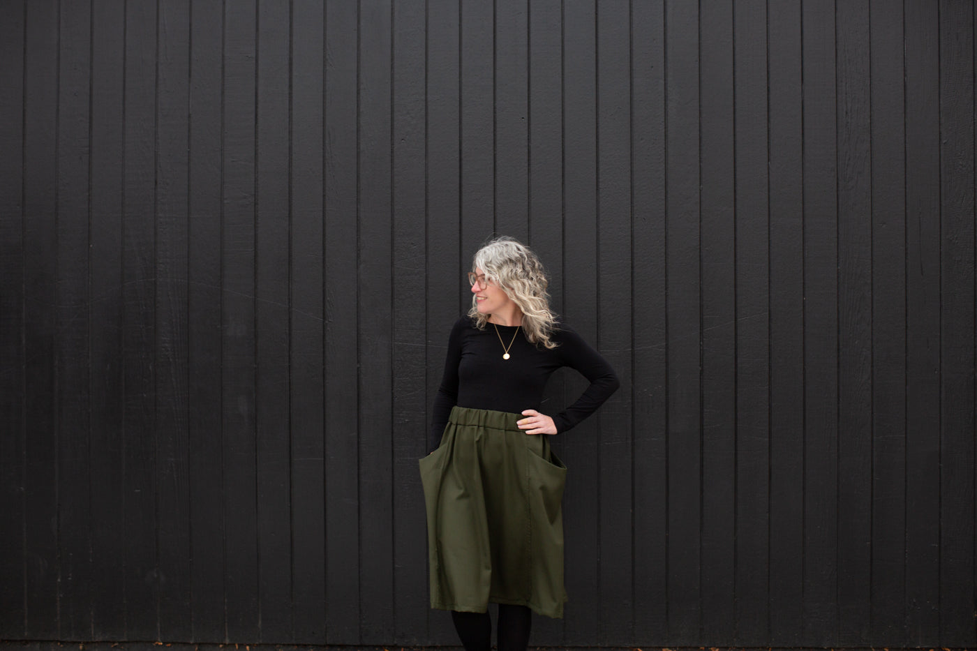Jaime standing against a black wall in a black long sleeve and olive colored skirt with her hands in her pockets looking off to the right.