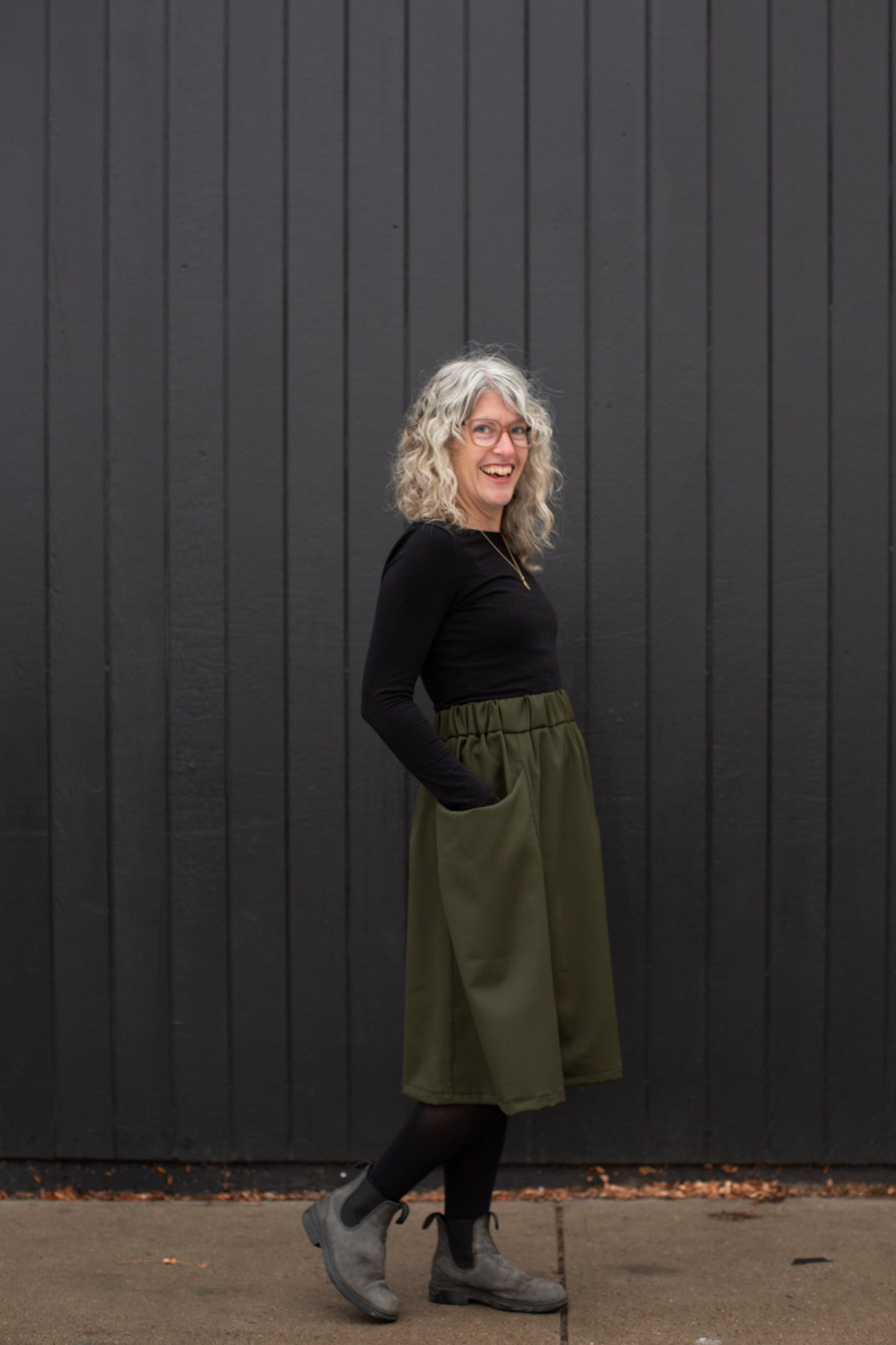 Jaime standing against a black wall in a black long sleeve and olive colored skirt with her hands in her pockets looking at the camera smiling.