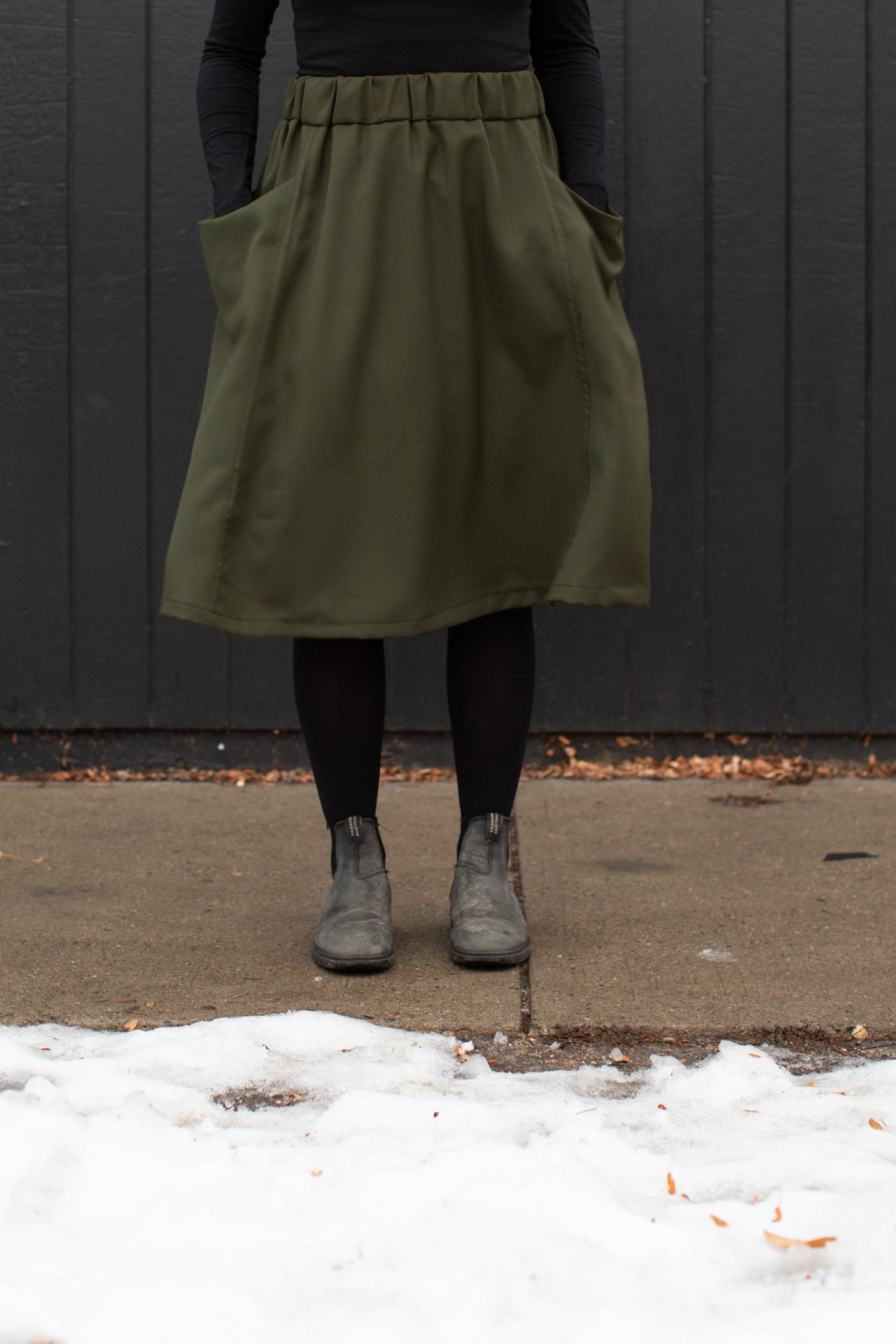 Mid waist to feet image of Jaime standing against a black wall, wearing an olive green skirt, black leggings and shoes with her hands in the pockets.  Jaime is standing on a sidewalk with snow in the foreground.