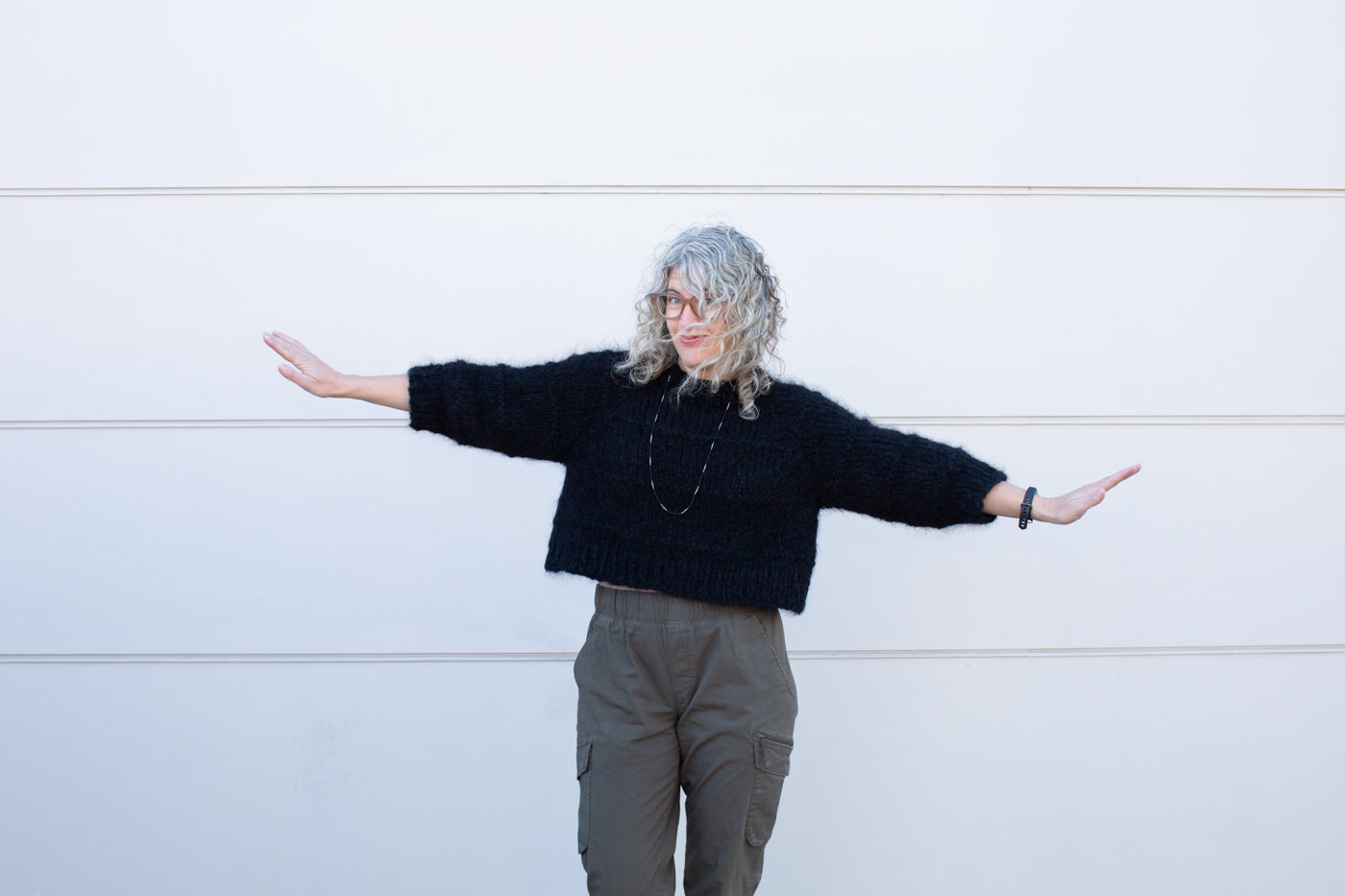 Jaime wearing a black fuzzy wool sweater with her arms out, wearing army green pants standing in front of a white wall.