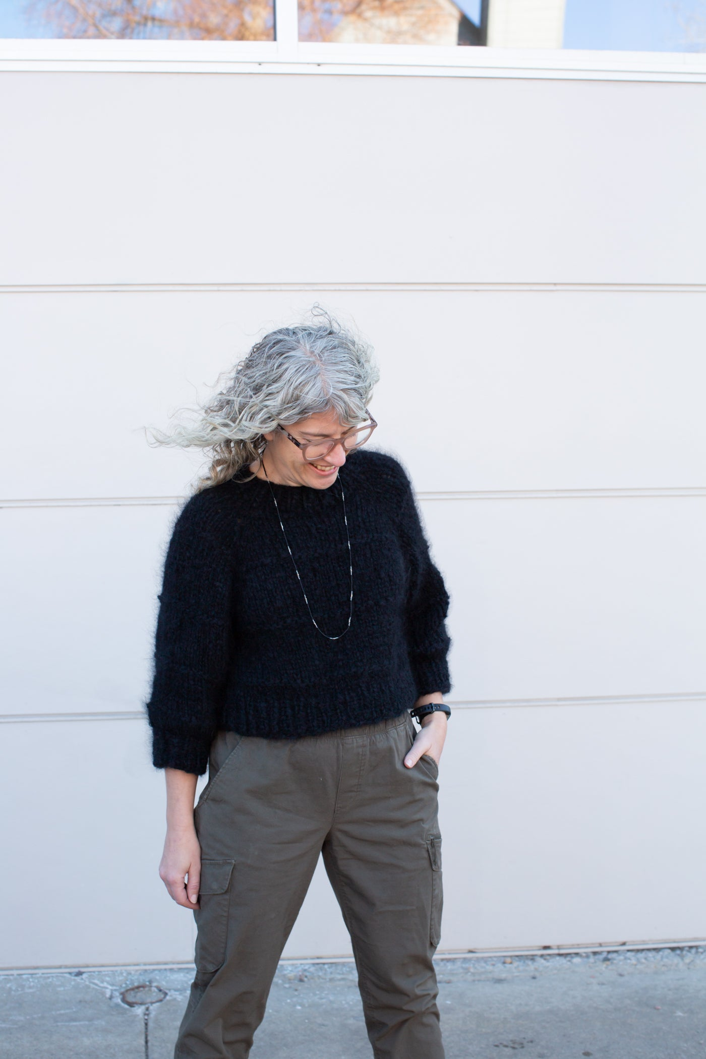 Jaime standing in front of a white wall with a black wool sweater, left hand in her pocket and green pants.  Jaime is wearing glasses, smiling and looking down to the left.
