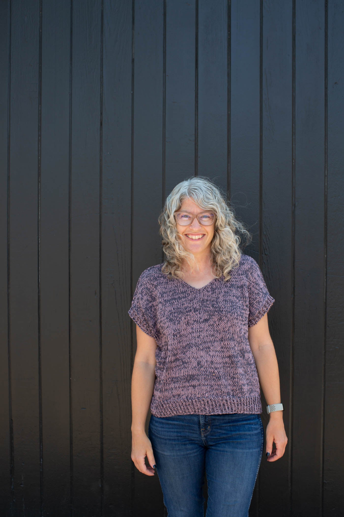 Jaime standing in front of a black wall, standing straight in front of the camera smiling.  Jaime is wearing a knitted Rift Tee in slate gray and mauve and blue jeans.