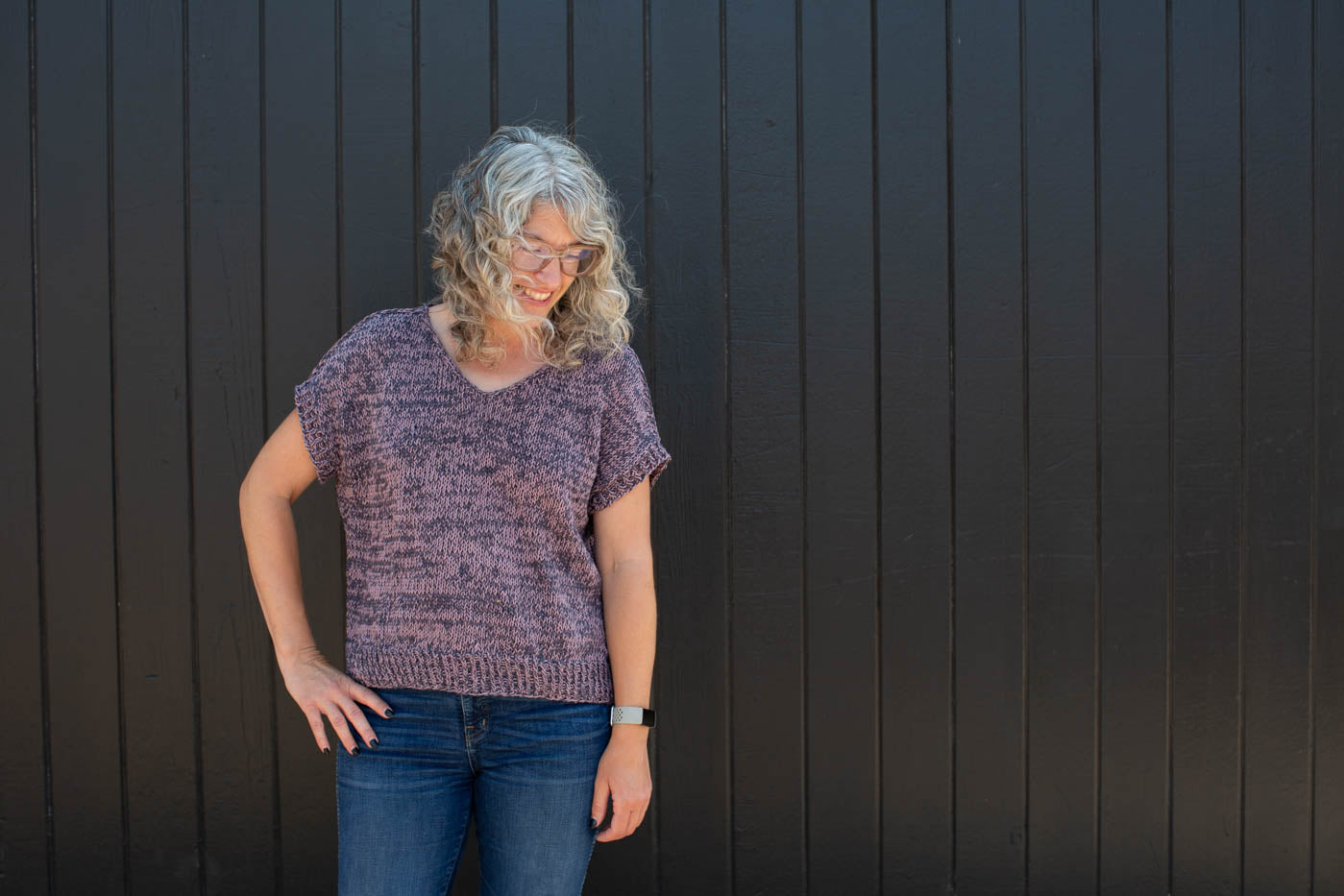 Jaime standing in front of a black wall wearing a knitted Rift Tee in slate gray and mauve with blue jeans.  Jaime is standing straight on looking down to her left with her right hand on her hip.