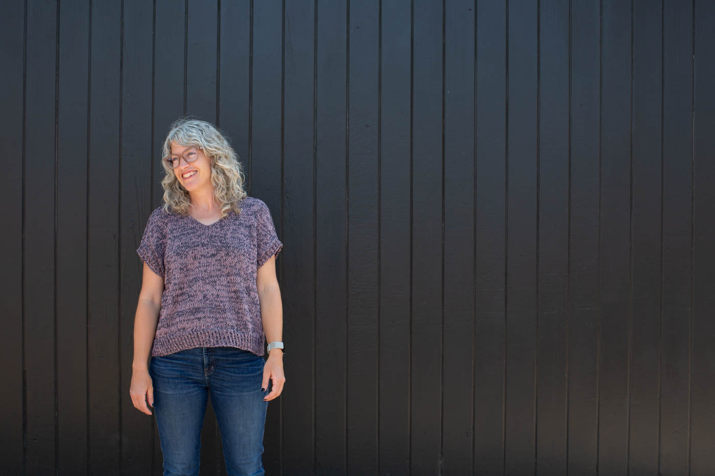 Jaime standing in front of a black wall wearing a knitted Rift Tee in slate gray and mauve with blue jeans.  Jaime is standing straight on looking down to her right with her hands by her side and smiling.