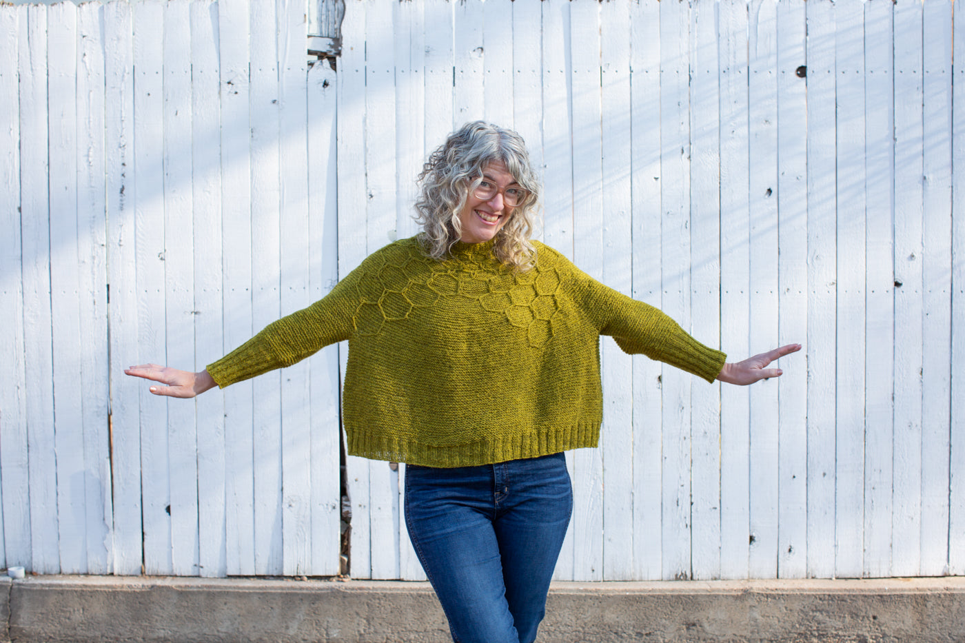 Jaime smiling, facing straight at the camera,  standing with arms out showing a yellow-green knitted sweater and wearing dark jeans.  The sweater has a honeycomb design on top part of the sweater.  The background is a white fence.