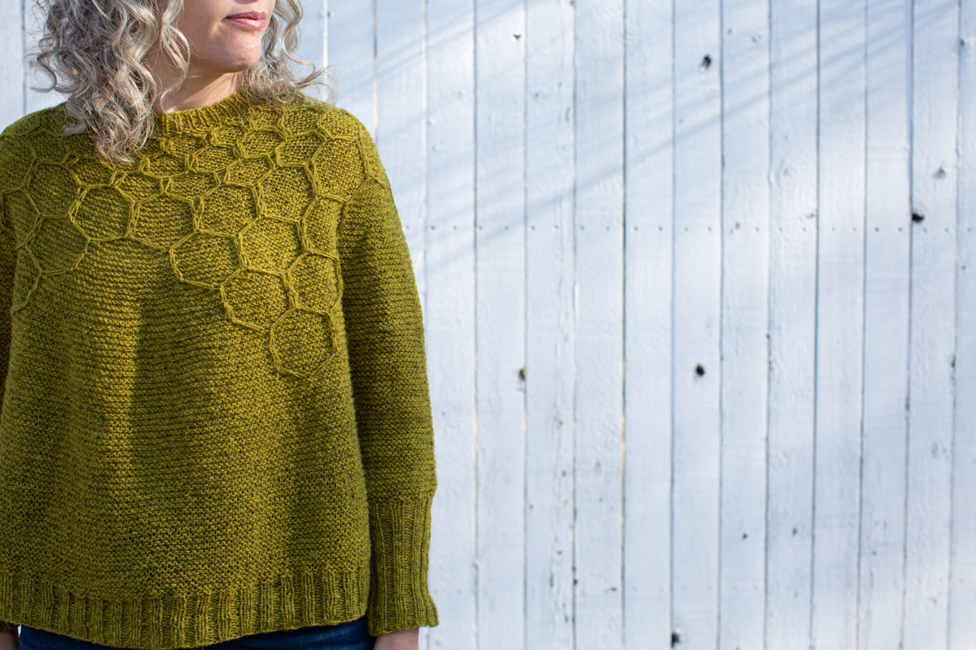 Jaime looking off to her left, camera angle is close up showing a yellow-green knitted sweater.  The sweater has a honeycomb design on top part of the sweater.  The background is a white fence.
