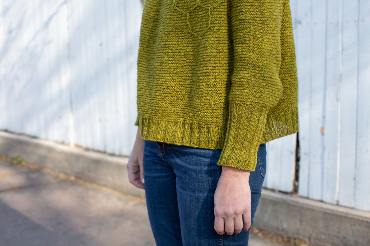 Closeup detail photograph showing the knitting on a yellow-green sweater on the sleeves and base.  The women is wearing white jeans and standing on a city sidewalk with a white fence behind her.