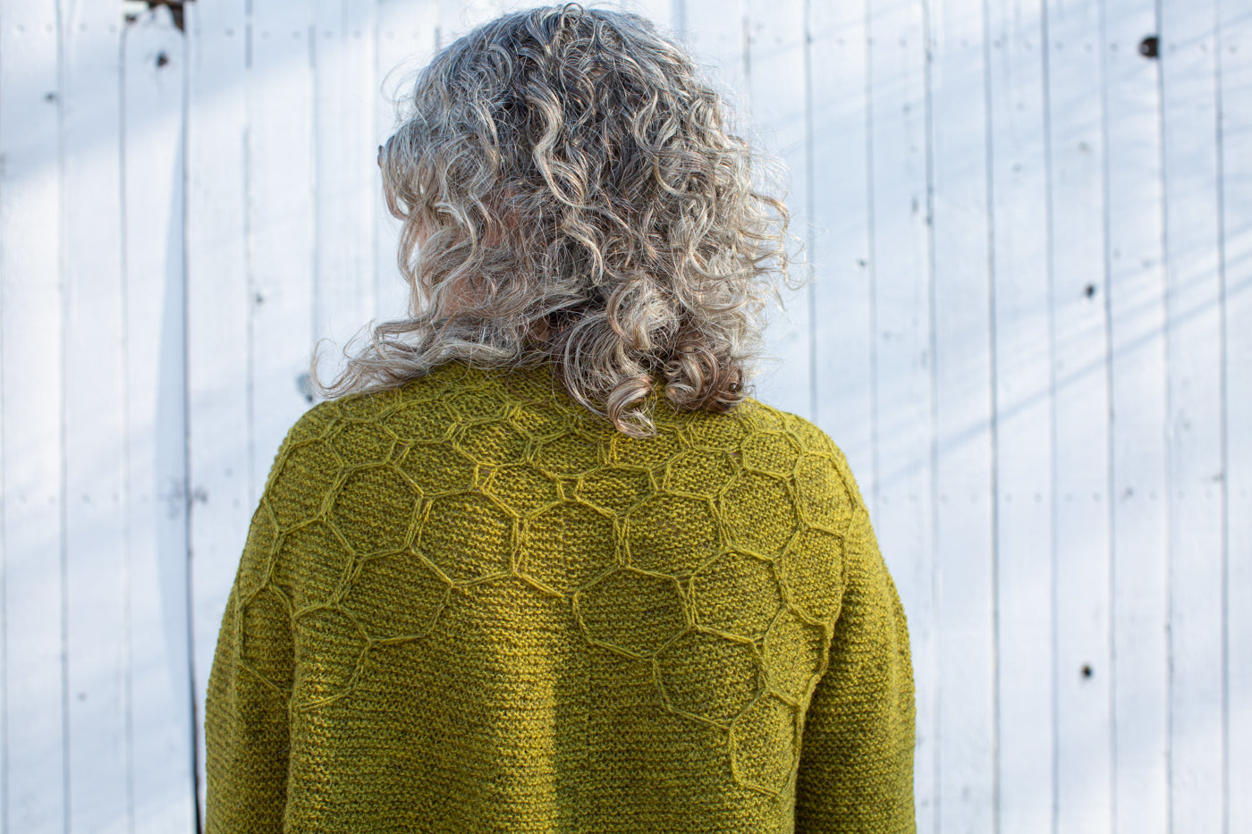 Jaime facing away from camera the camera crop is close up showing the honeycomb design on her yellow-green knitted sweater .  The background is a white fence.