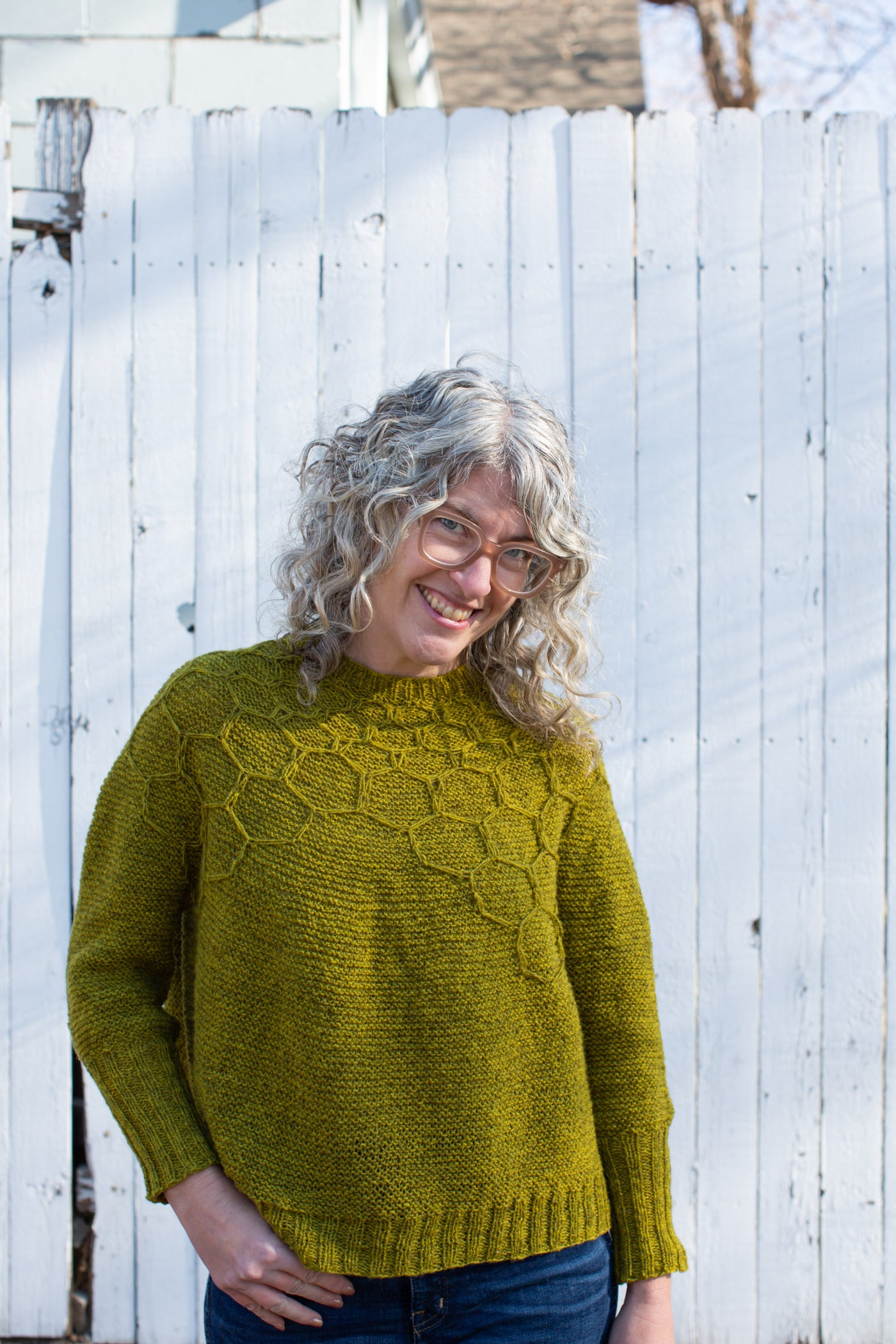Jaime smiling, facing straight at the camera,  standing one hand in her jean pocket and the other to her side, showing a yellow-green knitted sweater and wearing dark jeans.  The sweater has a honeycomb design on top part of the sweater.  The background is a white fence.