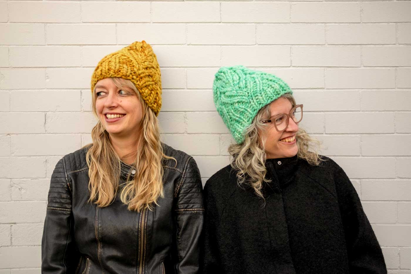 Amber in a yellow Neighborhood Holiday hat and Jaime in a mint green one, standing against a white brick wall.
