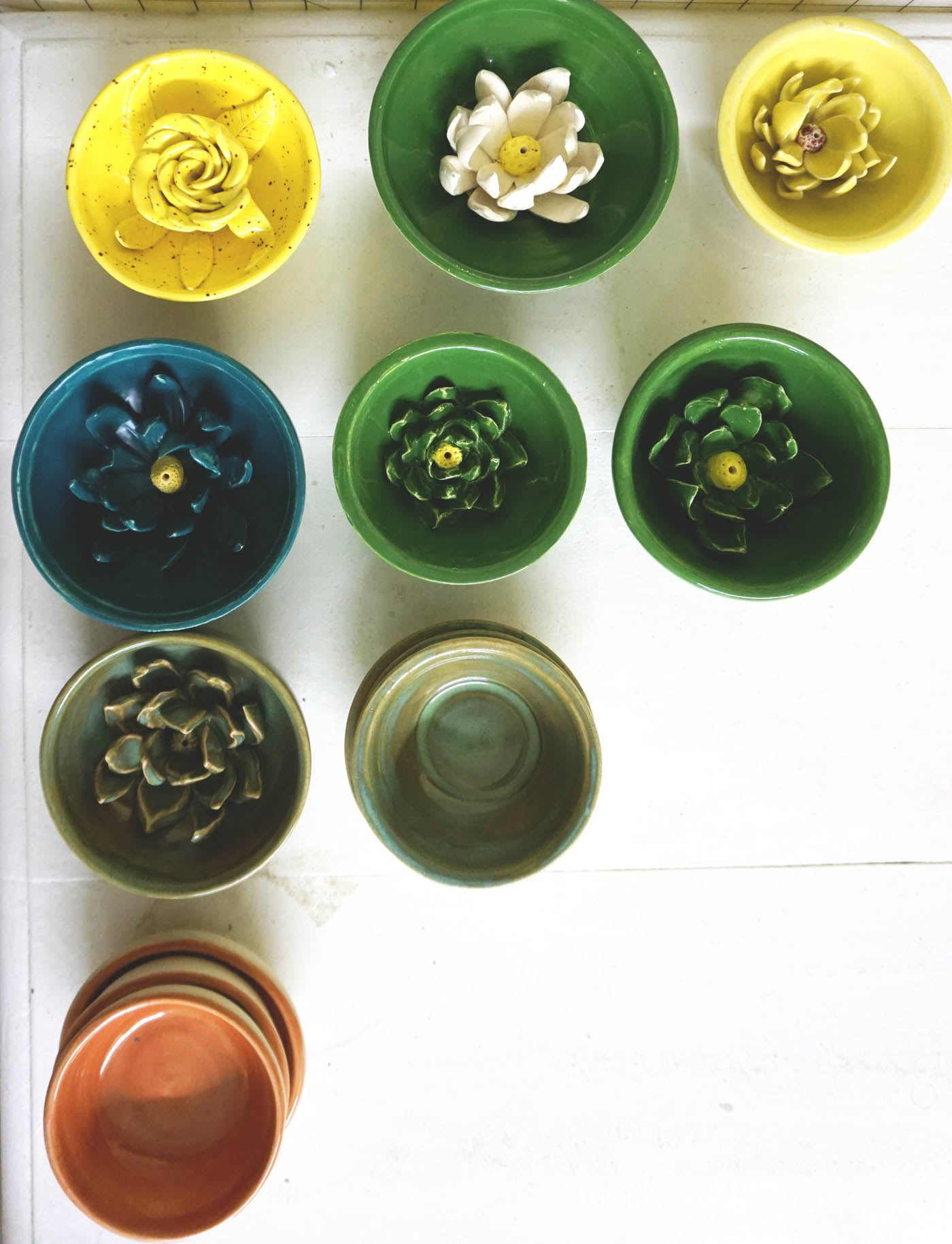 Pottery lined up in rows in multiple colors, photo is taken looking straight down.