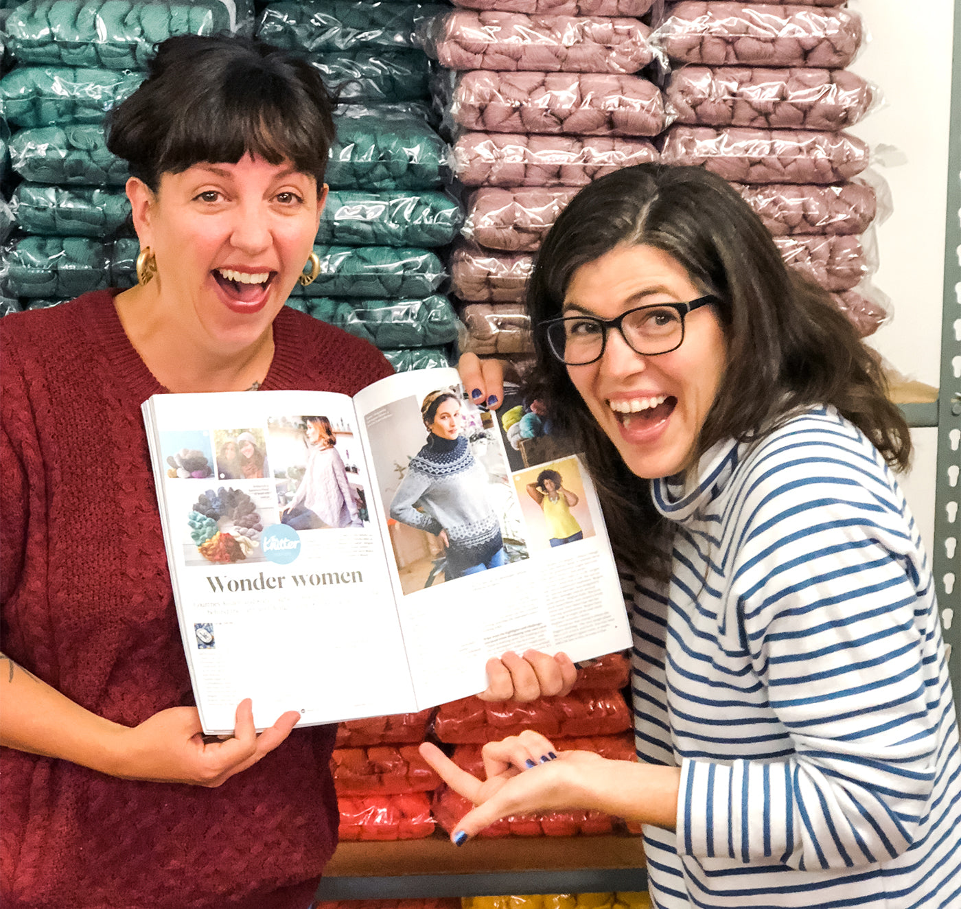 This is an image of two women holding a book open laughing in front of a wall of yarn.