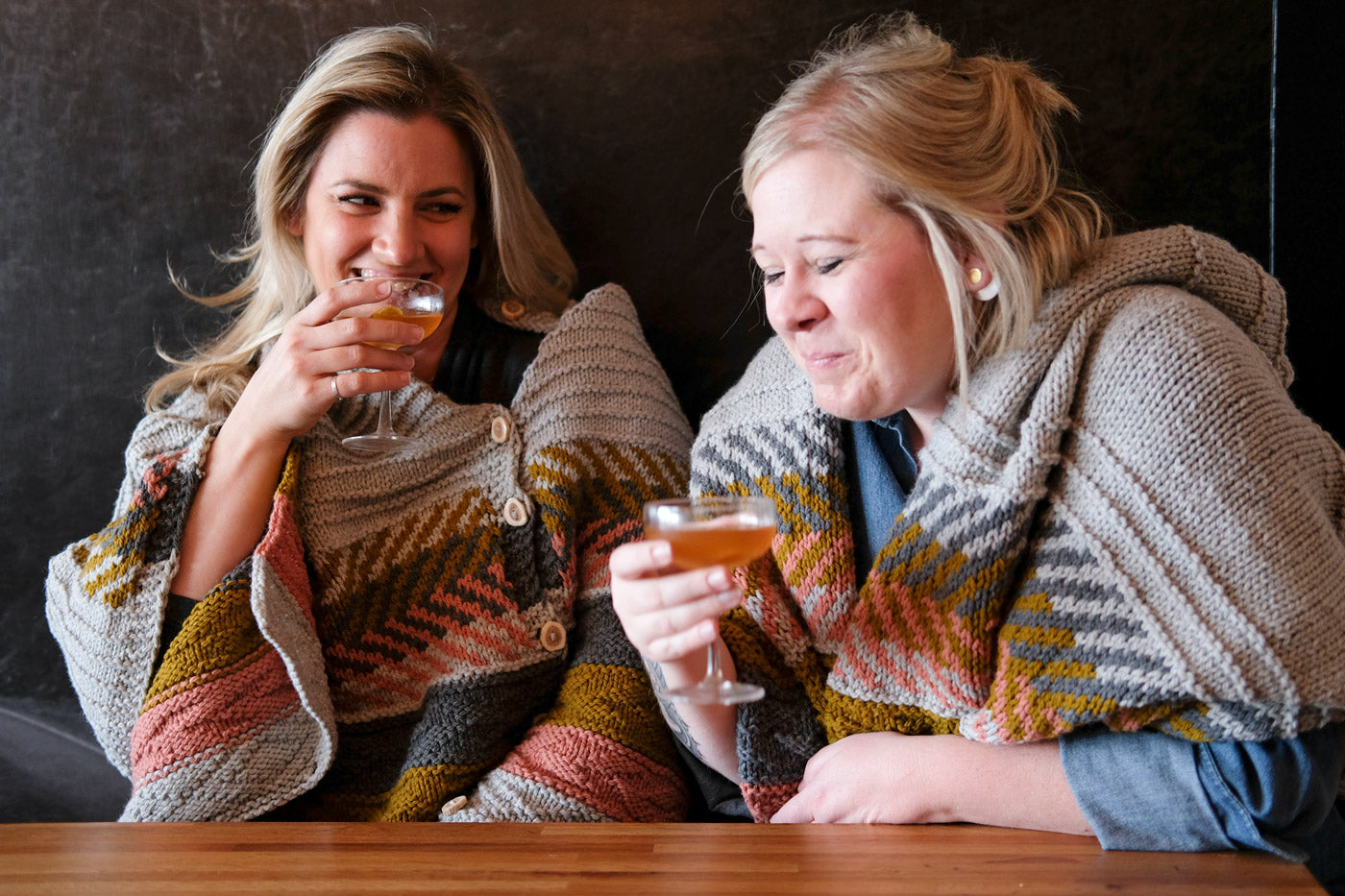 Kelly and Heather sipping cocktails in their Om shawls