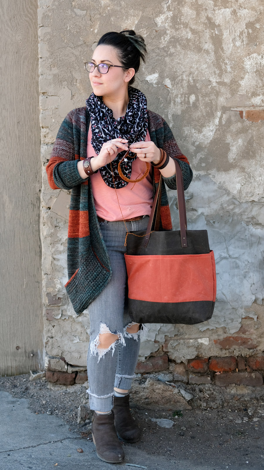 Rae knitting while holding the red and navy Oberlin Tote
