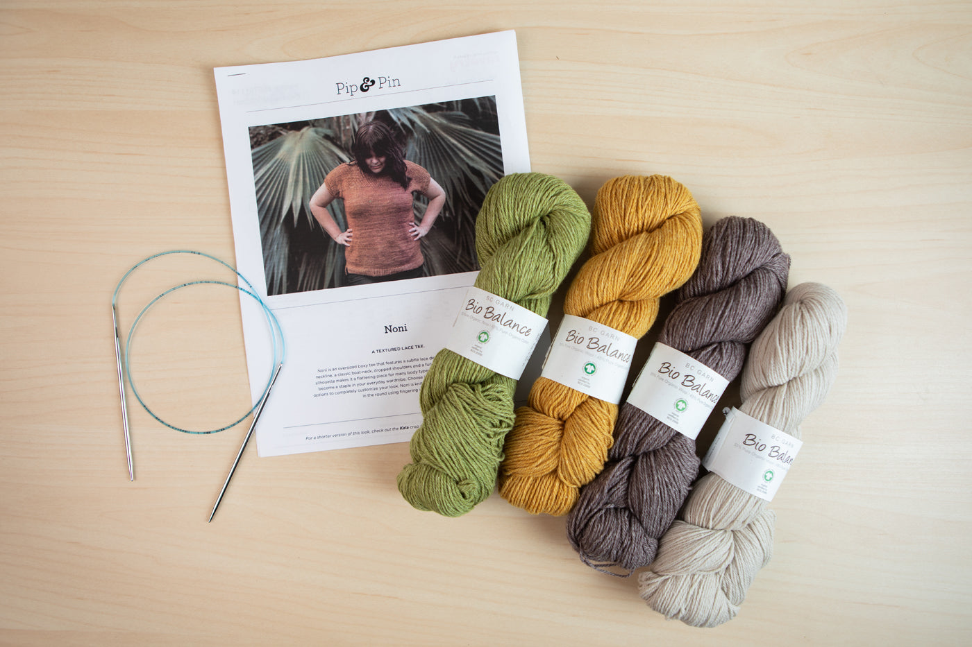 Sarahs chosen Noni pattern, four colors of BioBalance yarn and a set of knitting needles lay on a light wood background.