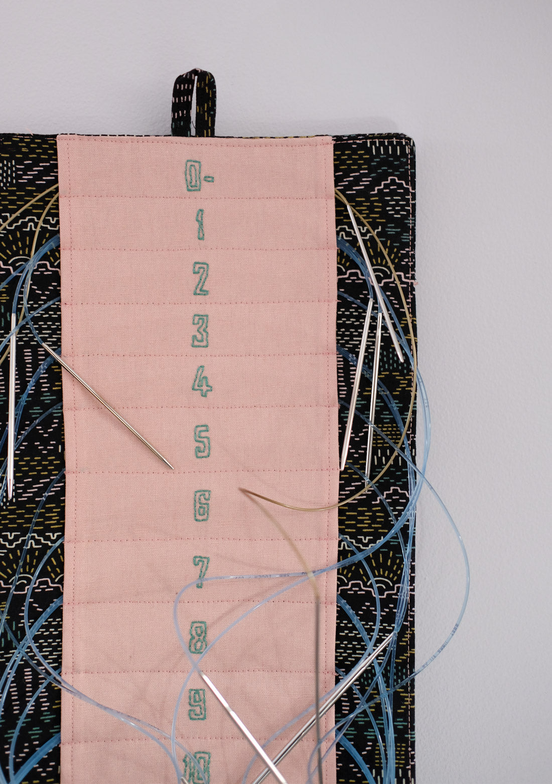 Close up photo of the pink and black knitting needle minder with hand embroidered needle numbers