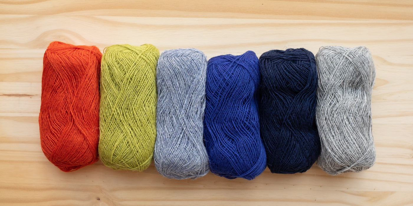 Lopi skeins in different colors lined up in a lay flat image with a birch wood background.  The colors from left to right are bright orange, light grass green, light blue, colbalt blue, navy and heather grey.