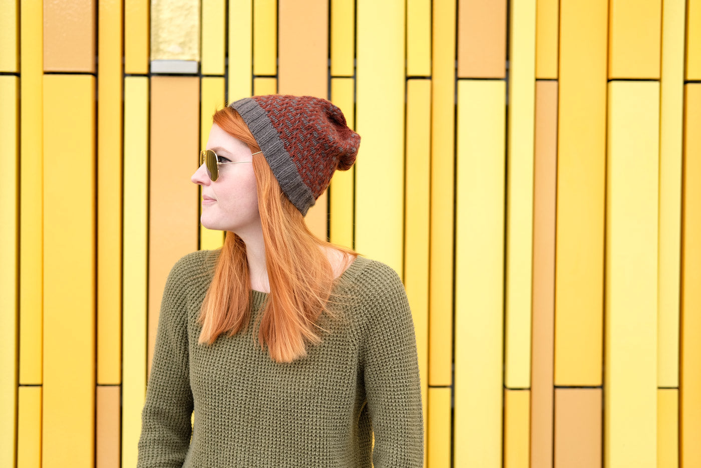 Lauren in sunglasses and her Tincture hat in front of bright yellow wall