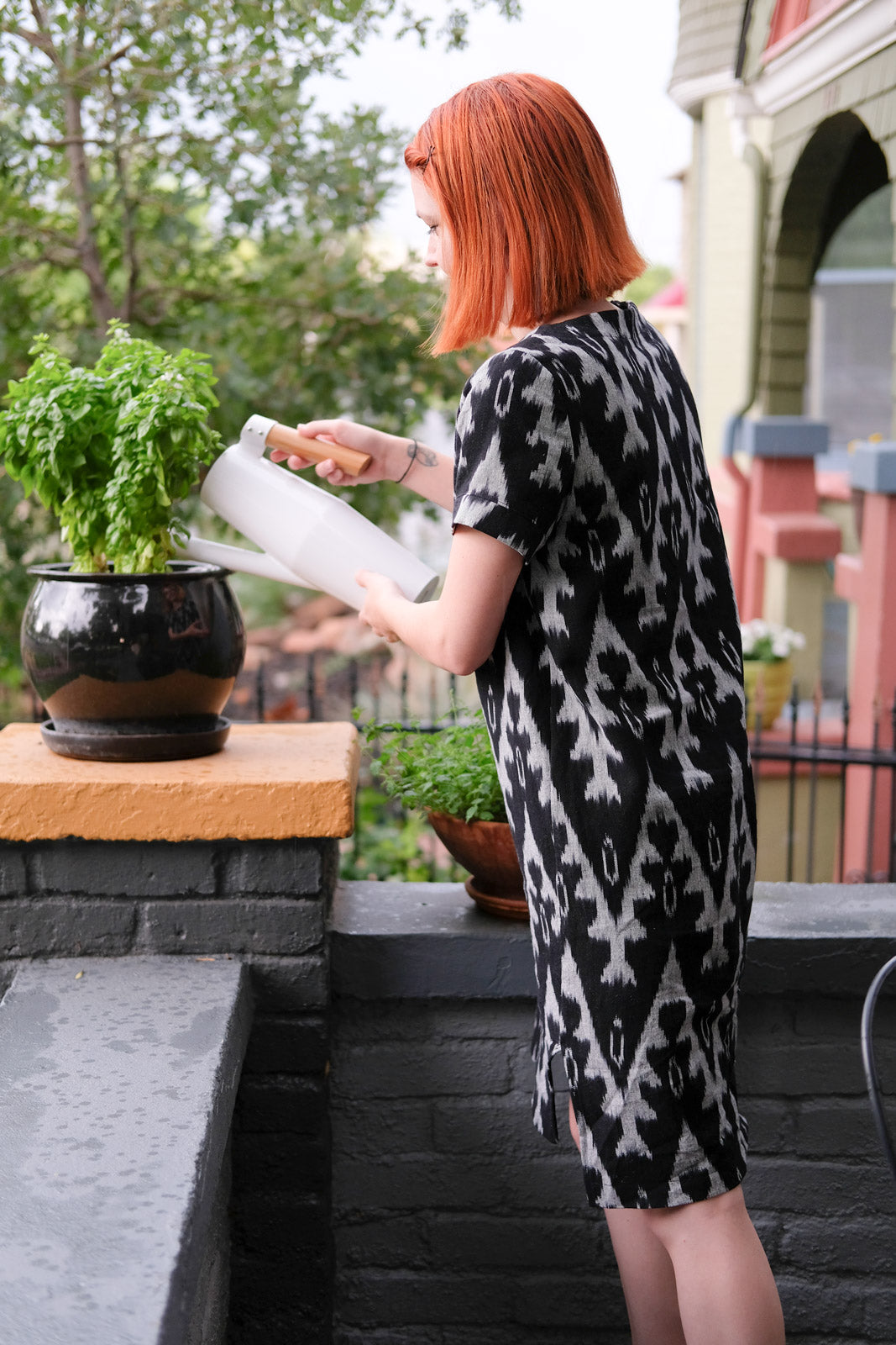 Lauren watering the plants in her Inari Tee Dress by Named Clothing