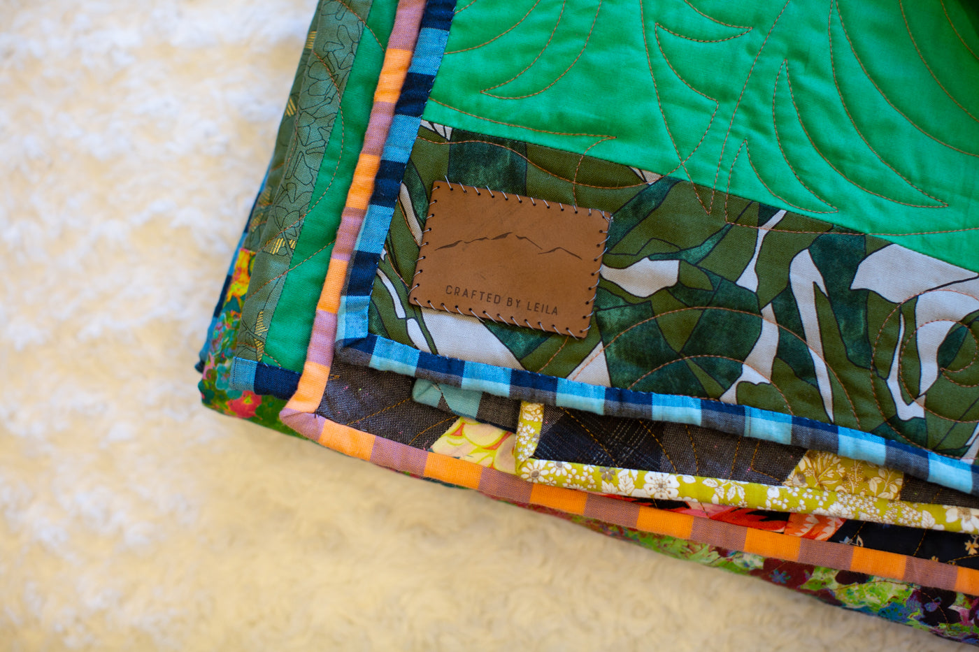 Layflat image of quilt on a white fuzzy background.  It is the corner of the quilt that has a light green patch above and a darker leaf green a pattern below.  The blanket has has a leather patch that says made by Lelia