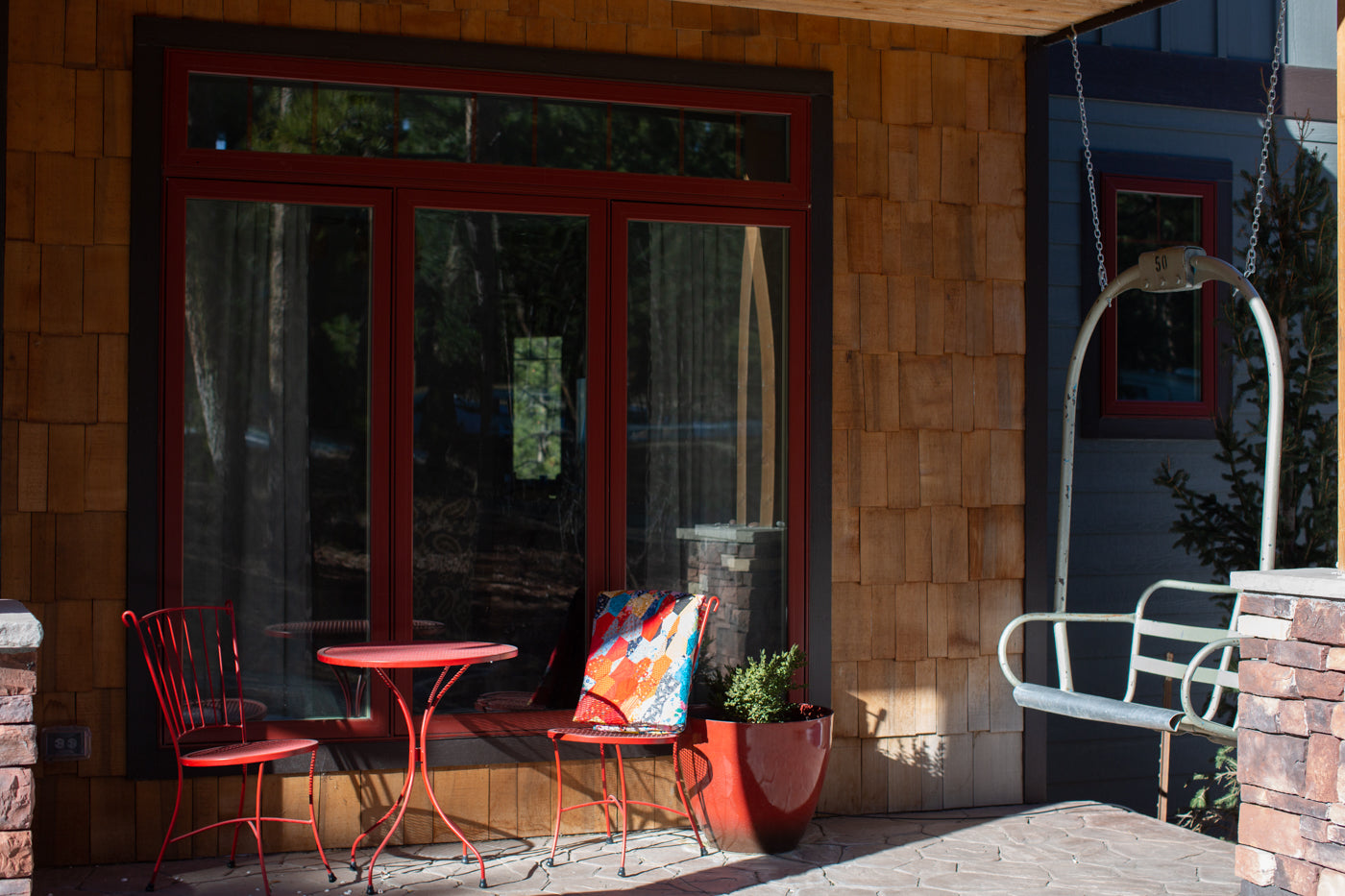 Front porch with a red table and chair with a multi colored quilt folded up hanging over the right chair in the sun.