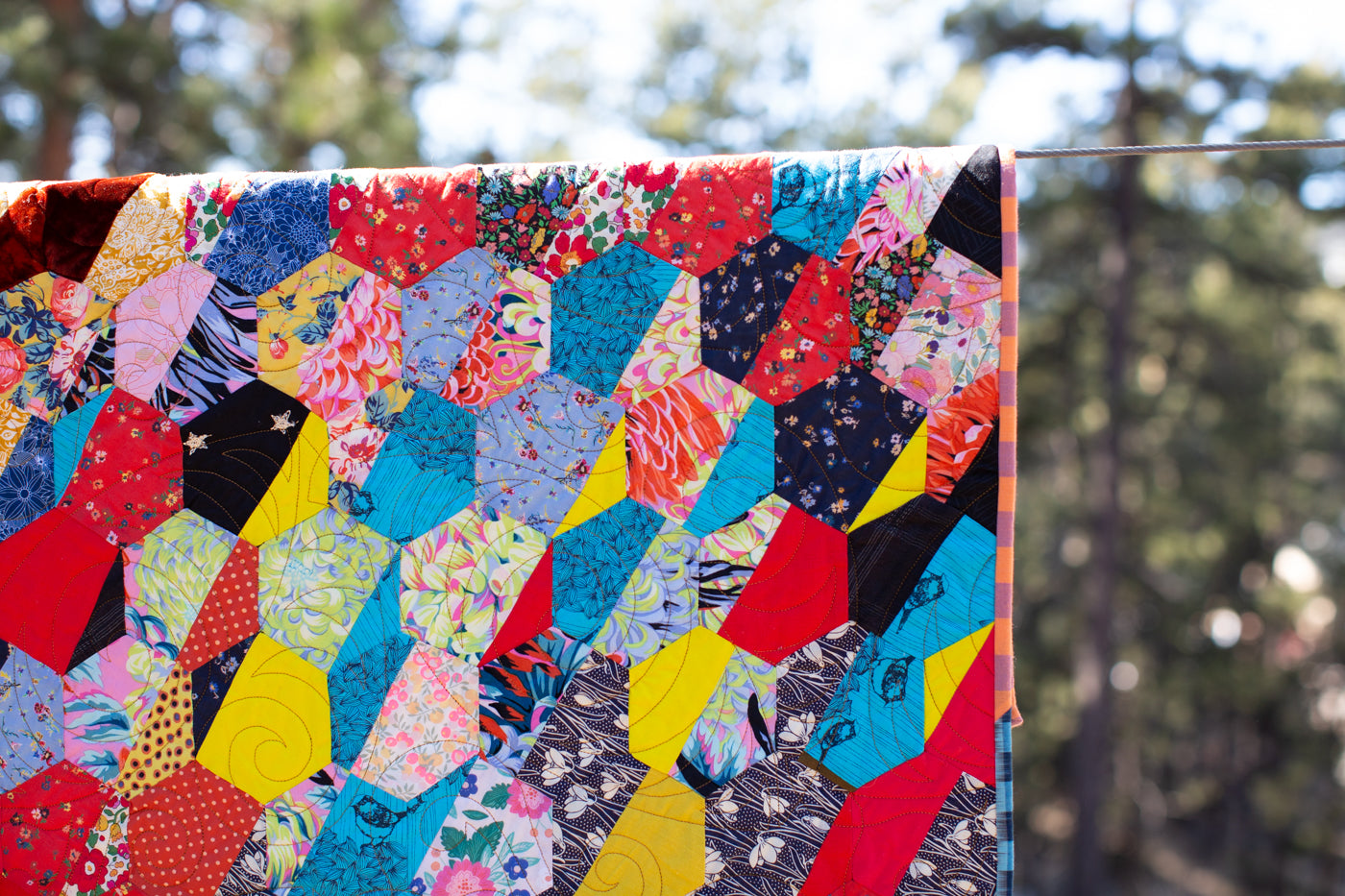 Close up of quilt with colorful geometric blocking background is evergreen trees.