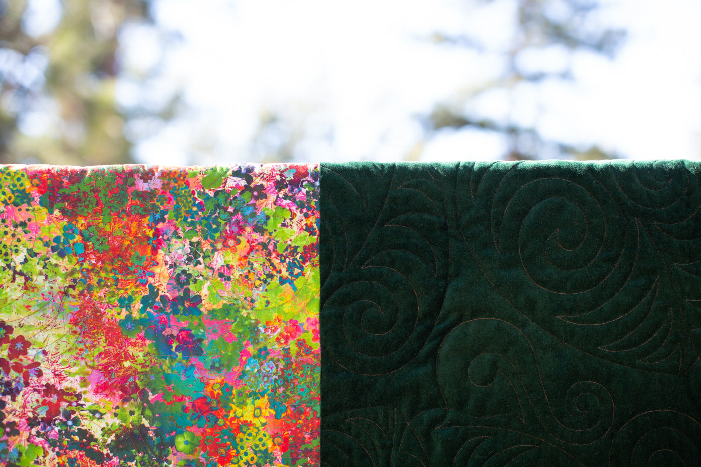 A close up photograph of a quilt hanging up with blue sky behind.  The is two big squares left side is bright colorful flowers, right side is dark green lush velvet.  Image is up close to show the quilting pattern.