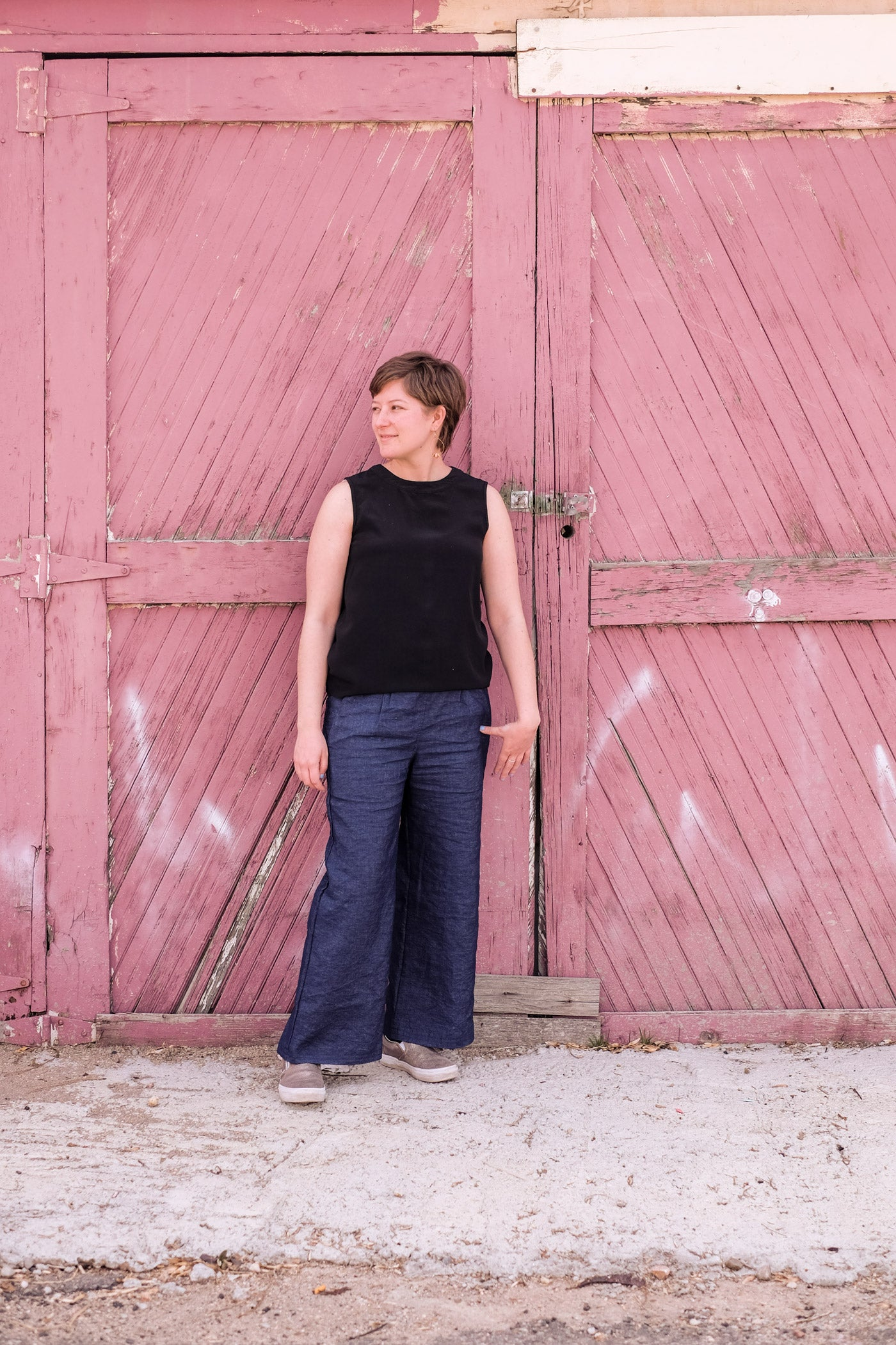 Lucy standing in front of a weathered red barn door wearing her indigo linen Emerson trousers