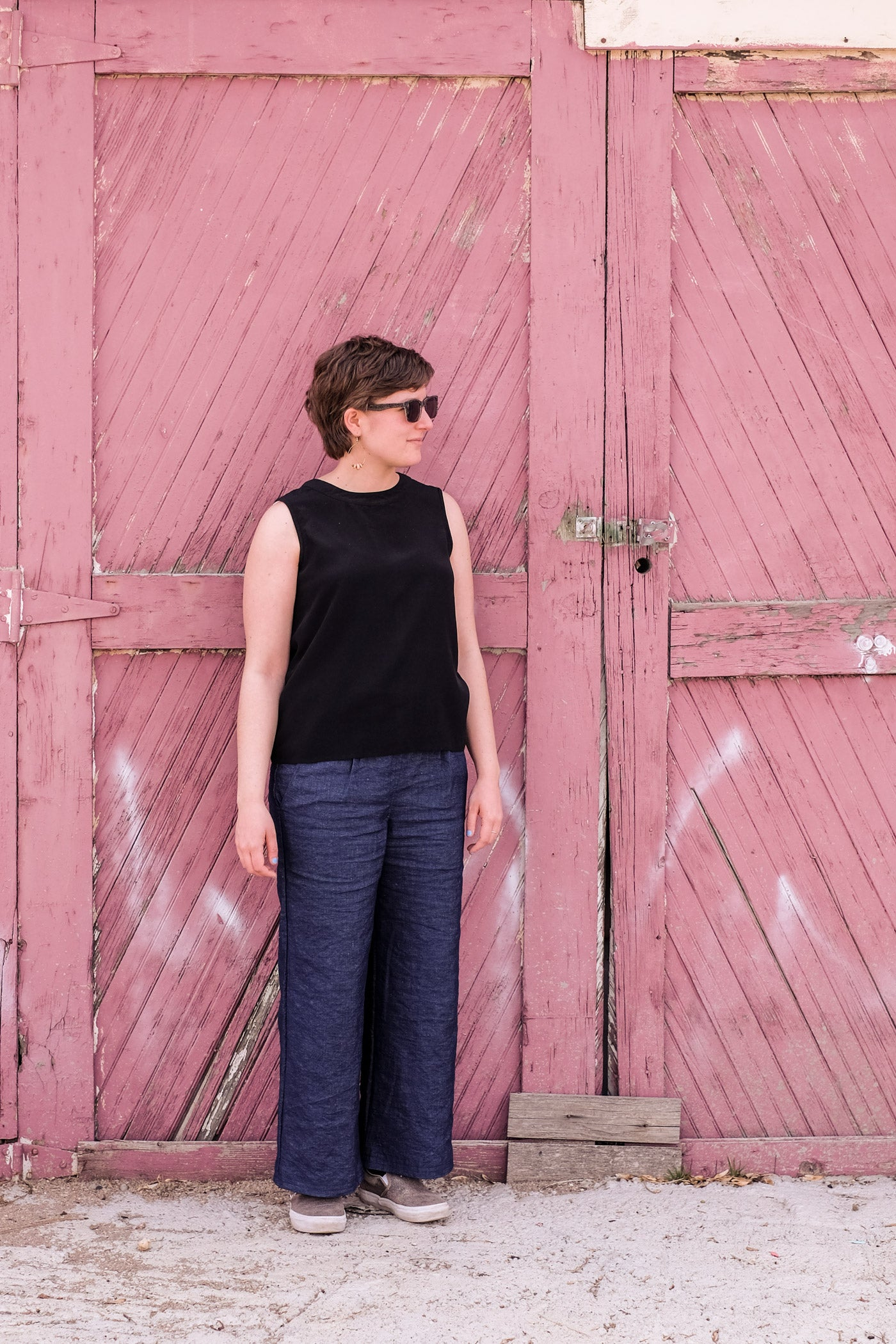 Woman standing outside a weathered red barn door, wearing sunglasses, a black tank top and wide legged indigo linen trousers.