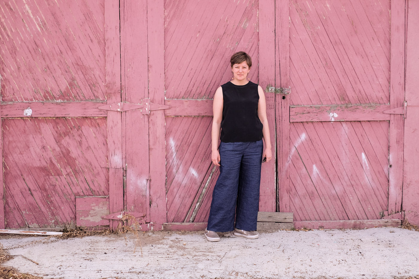 Lucy wearing her indigo linen trousers, she stands in front of a weathered barn door.
