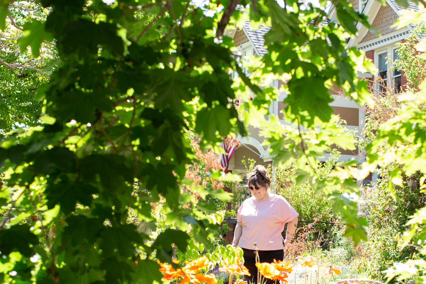 Marta wearing a light pink top, black jeans looking down at the big bright orange flowers blooming.  The photograph is taken looking through a green tree in the sunlight to Marta at a distance.  The tree is framing Marta in the photograph.