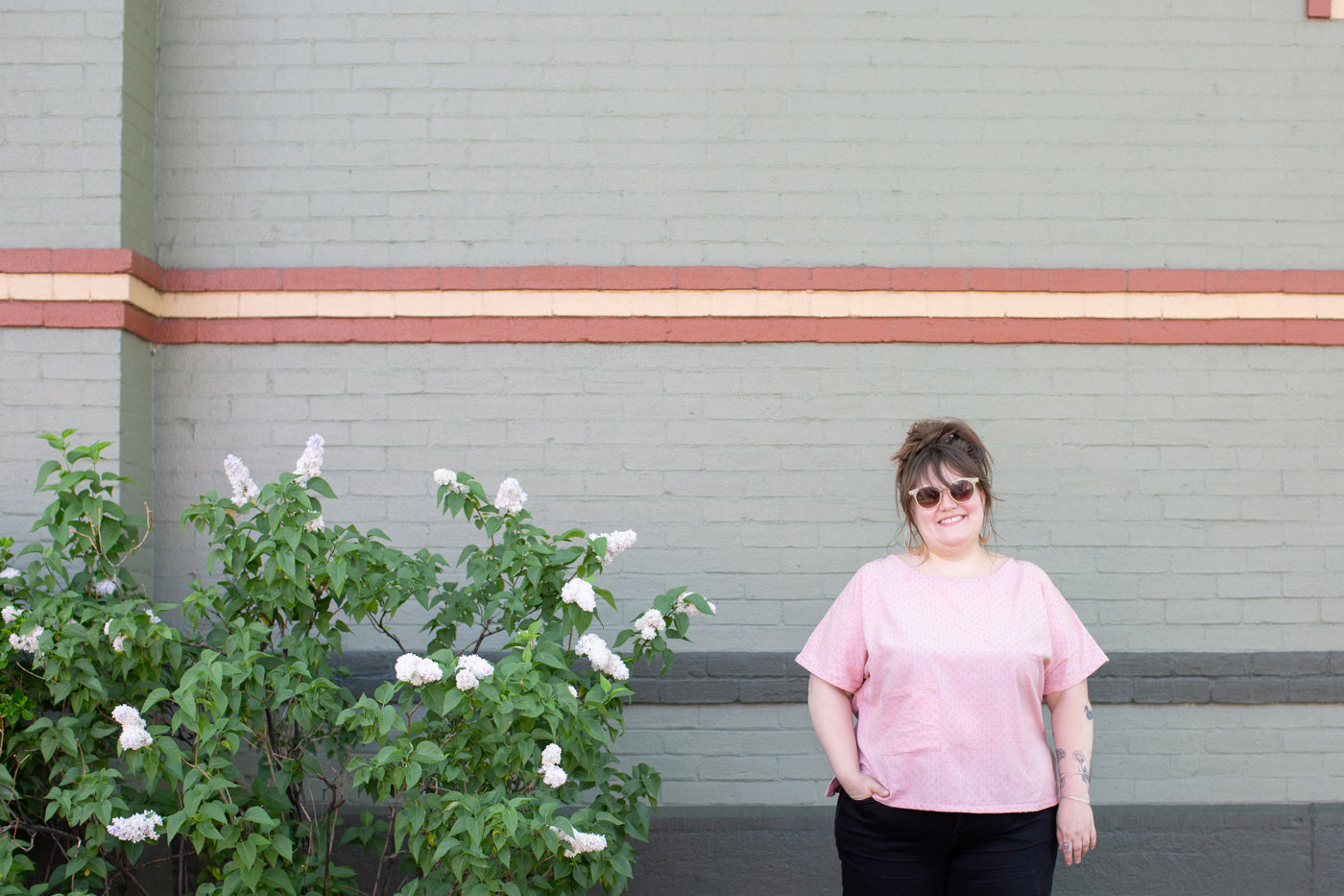 Marta wearing a pink shirt, black jeans, sunglass looking at the camera smiling.  To the right of Marta is a green bush with white flowers.  The wall behind Marta is a light green with stripes of color.  Above Marta's head is a red, light yellow, red pattern. Lower on the wall there are two dark green stripes of color parallel to the ground.