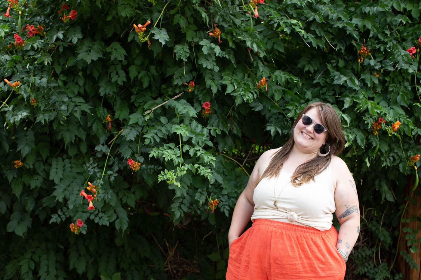 Women facing camera with sunglasses on with her hands in her pocket smiling.  Background is greenery with bright orange flowers that match the women's pants and the top is a cream colored tank top.