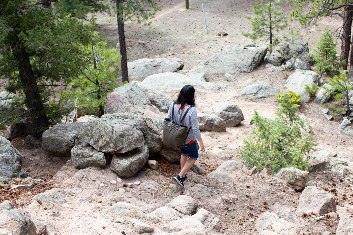 Girl walking down a rocky path wearing an evergreen backpack.  Girl's back is toward the camera.