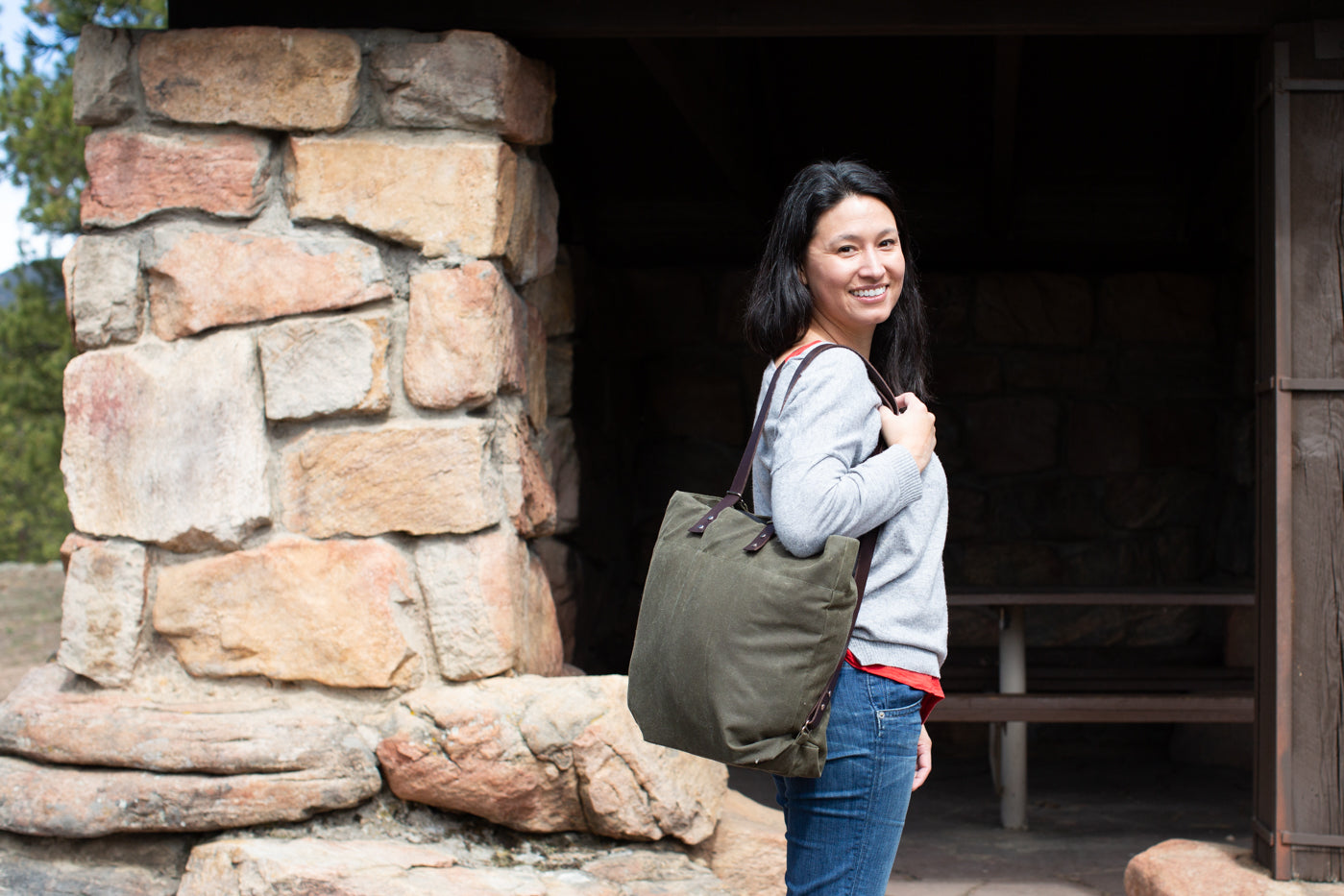 Photograph of women with a canvas bag with bag being over the shoulder.  Women is standing to the side in front of a stone picnic area.