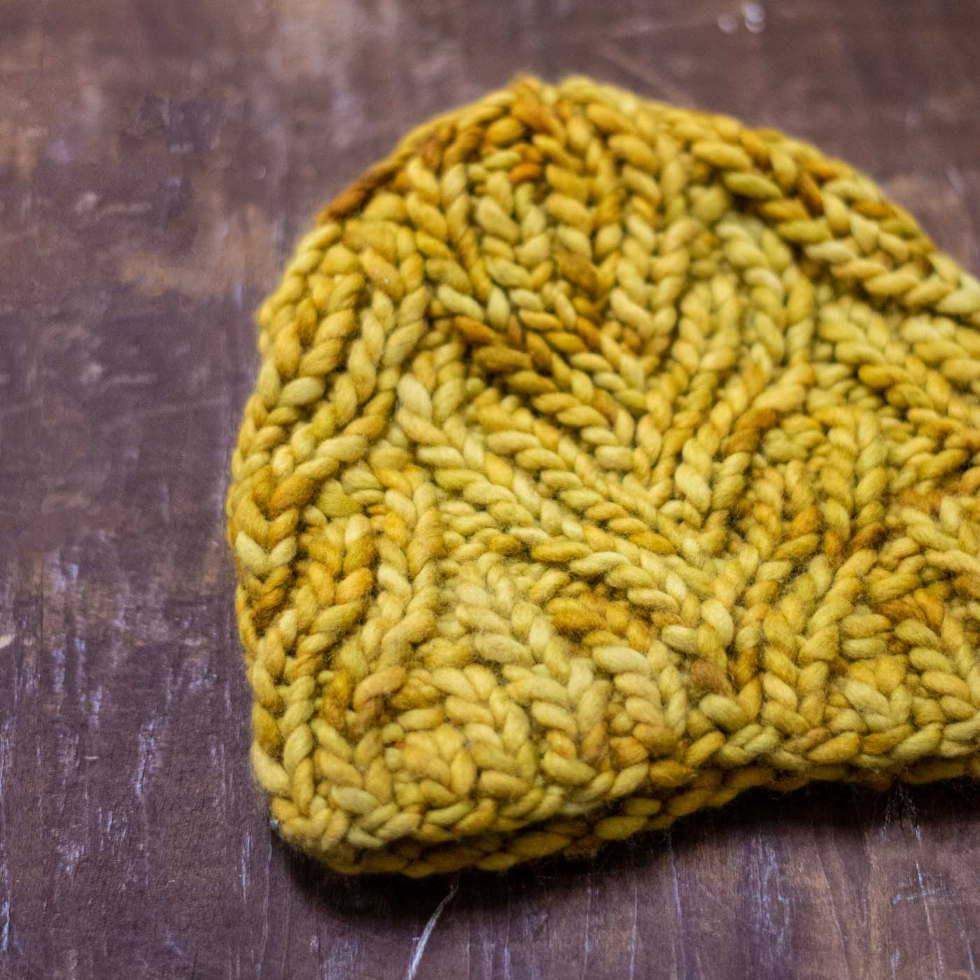 Mustard Neighborhood Holiday Hat laying flat on dark wood.