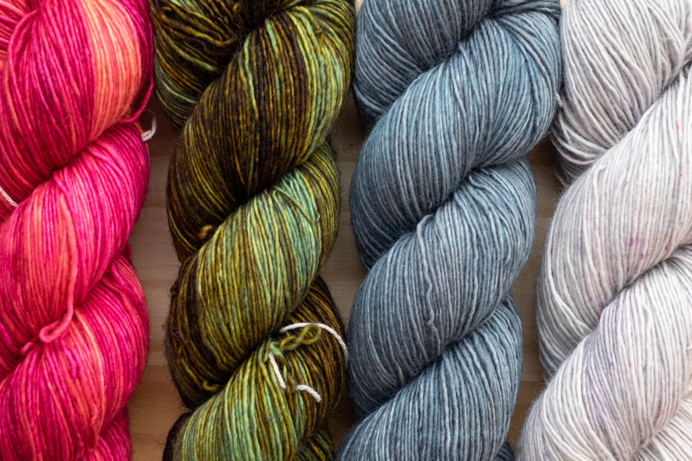 Neighborhood Fiber Co Skeins in lay flat image in red/orange, light green to dark green, light blue and a light silver.