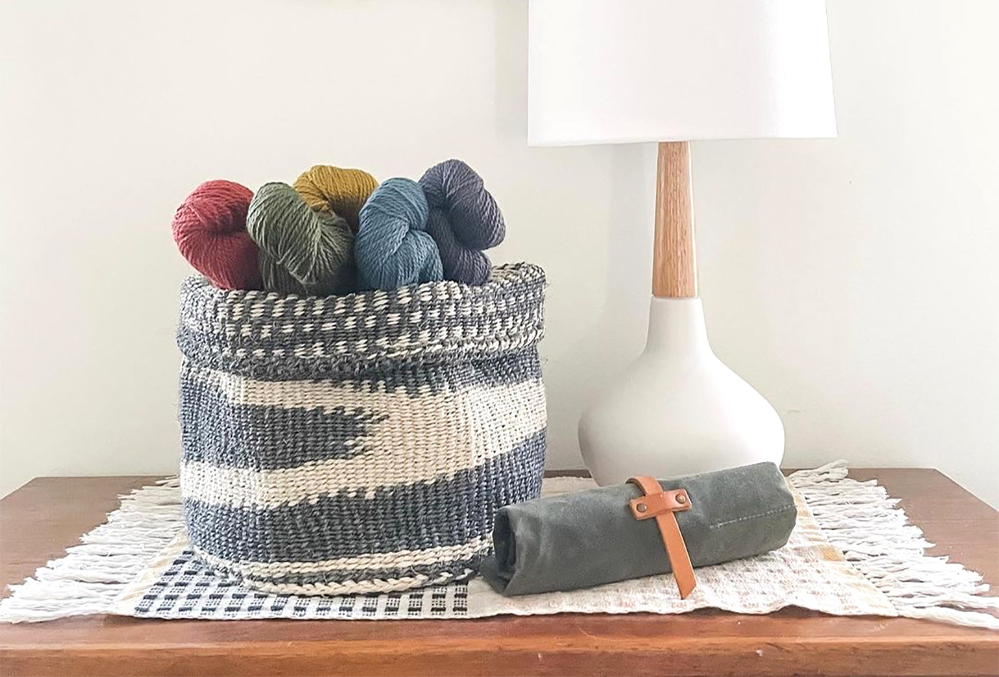 This is an image of a basket full of yarn sitting on top of a desk next to a lamp and a canvas roll for knitting needles