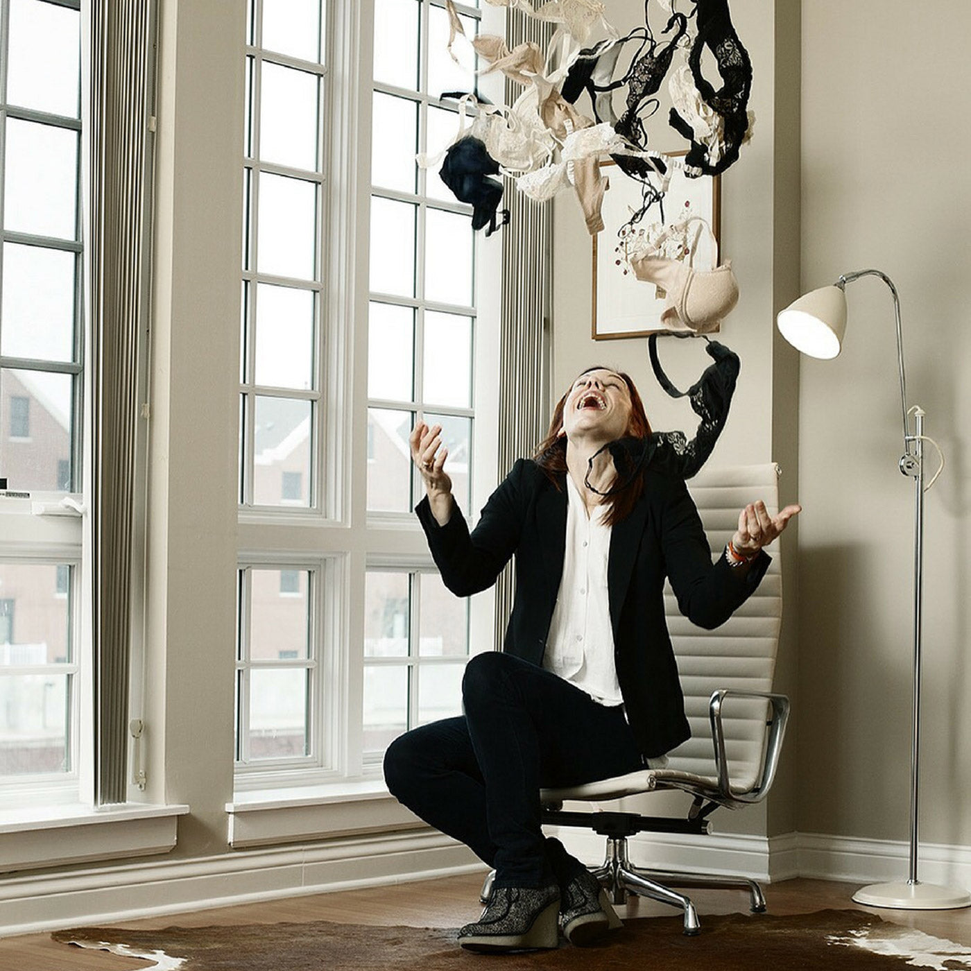 Norma Loehr sitting on the edge of a white chair, she has just tossed an armful of about 20 bras above her head and she is smiling looking up